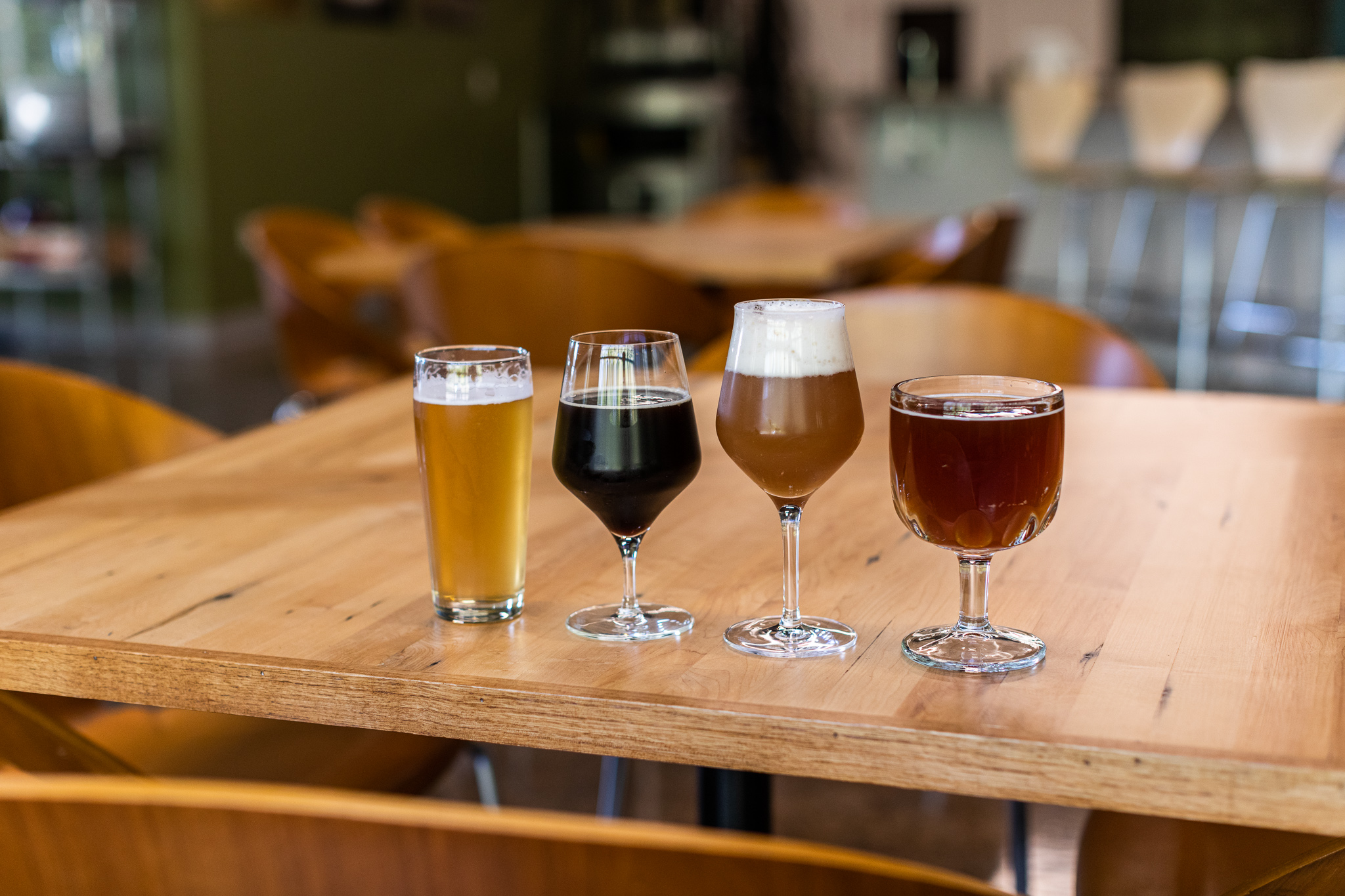 A light-colored beer in a pint glass, a dark stout in a stemmed glass, a taller stemmed glass with a slightly lighter cloudy beer and lots of head, and a brown beer with no head in a goblet-style glass. All four sit on a wooden table.