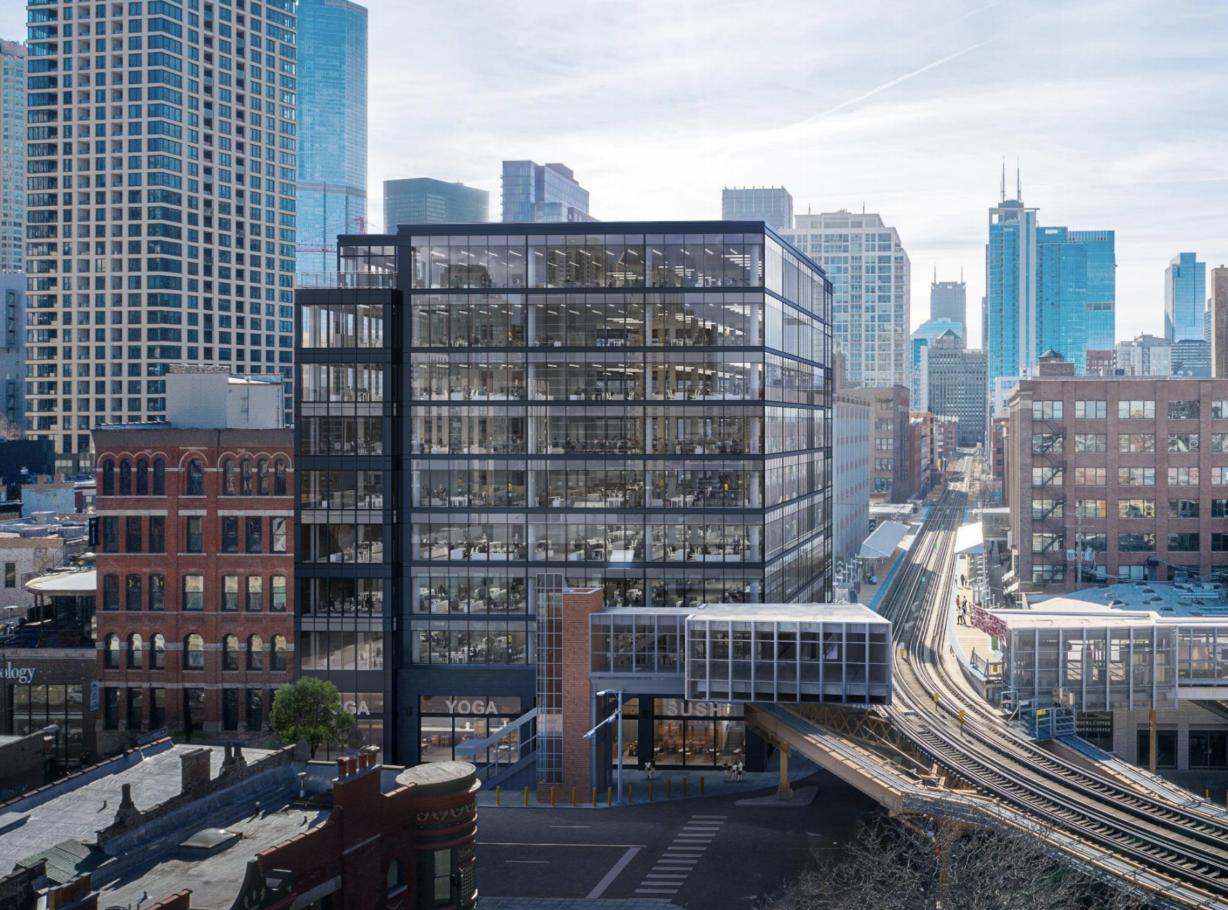 A rectangular glass and metal office building next to elevated train tracks. There are other tall buildings in the surrounding area.