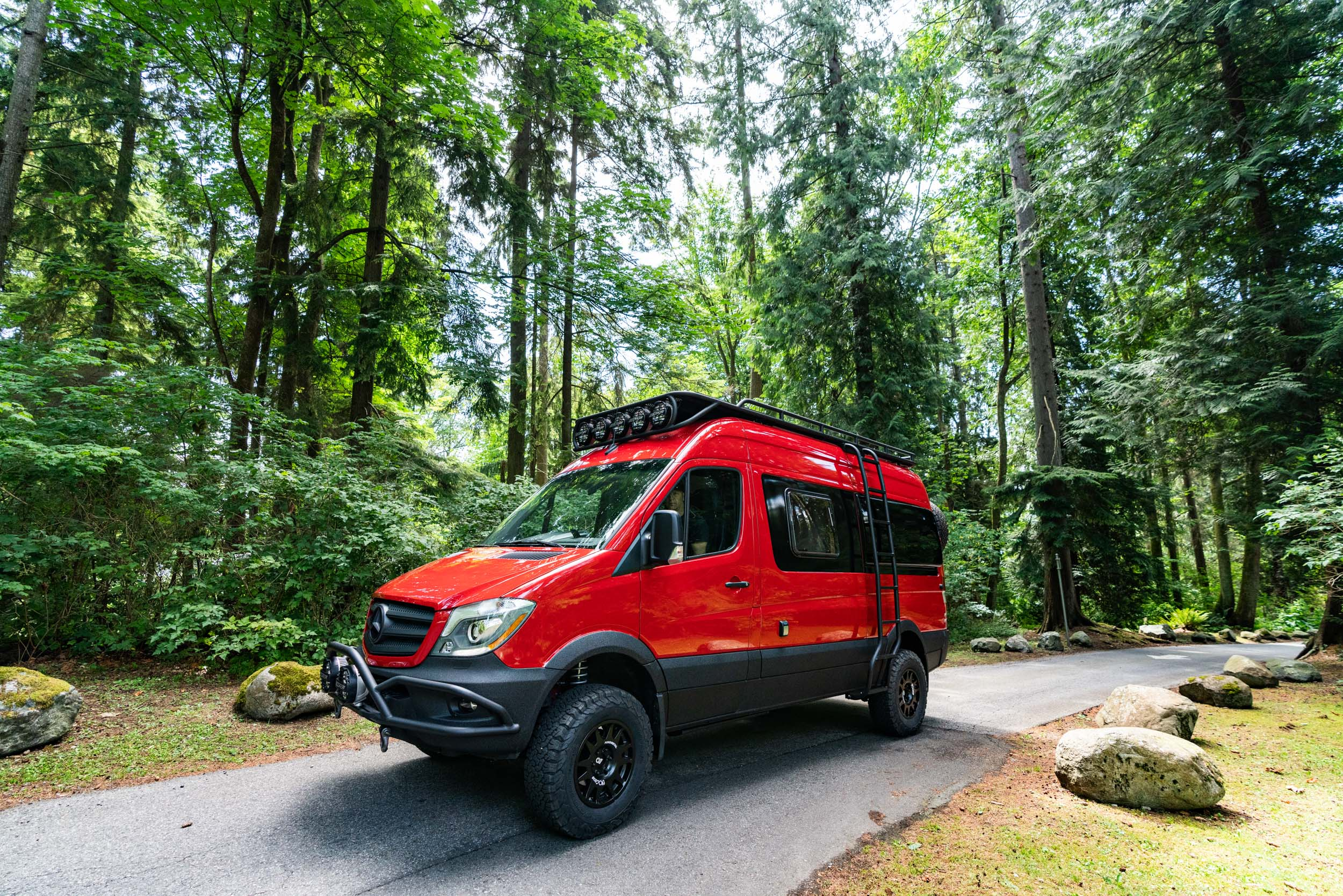 A bright red 144-inch Mercedes Sprinter van with black trim sits on a forest road with green trees all around it.