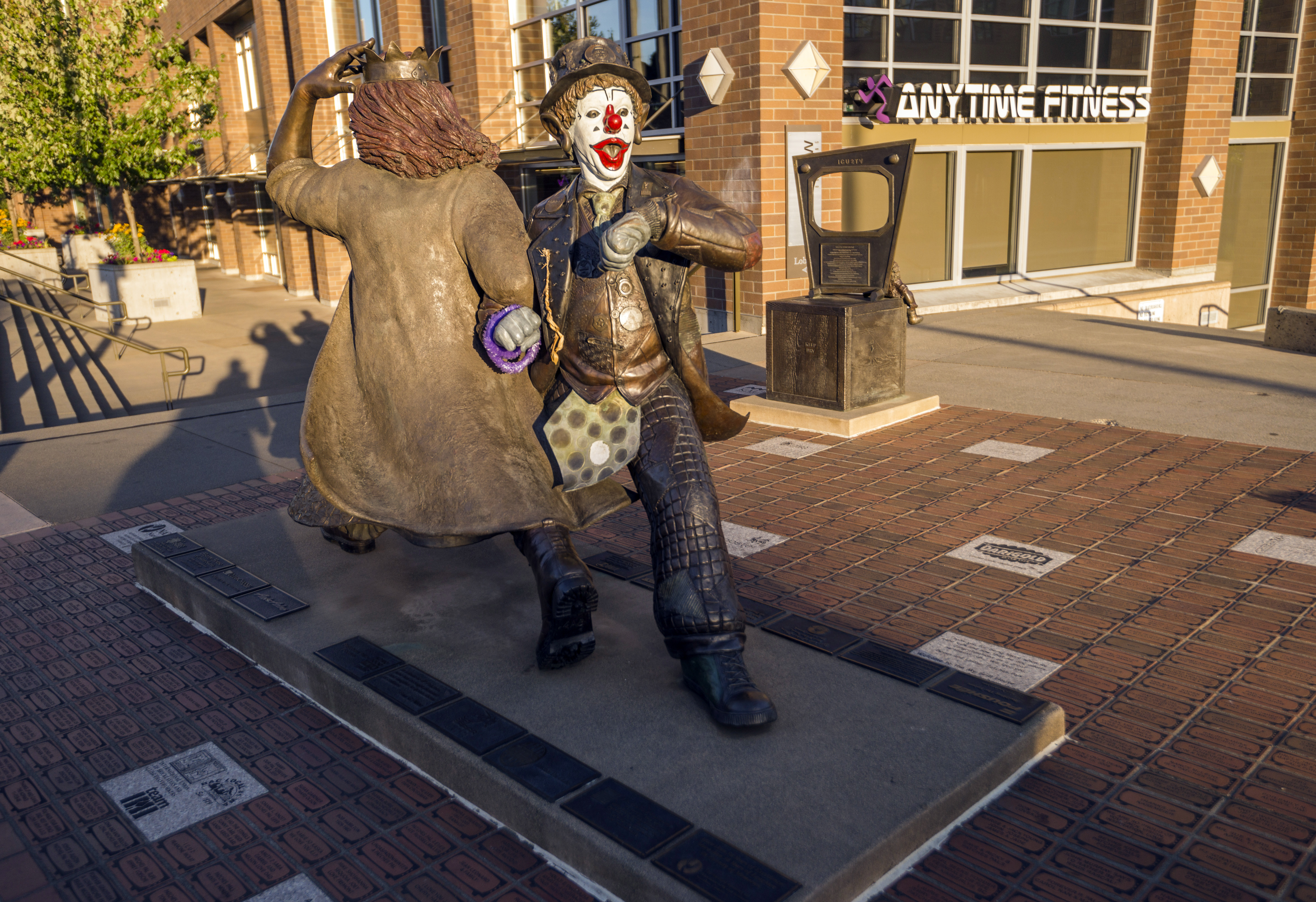 On a brick plaza in front of an Anytime Fitness, a statue of two people with arms linked. The person in front's face is in full clown makeup. (The other figure is facing the other direction.)