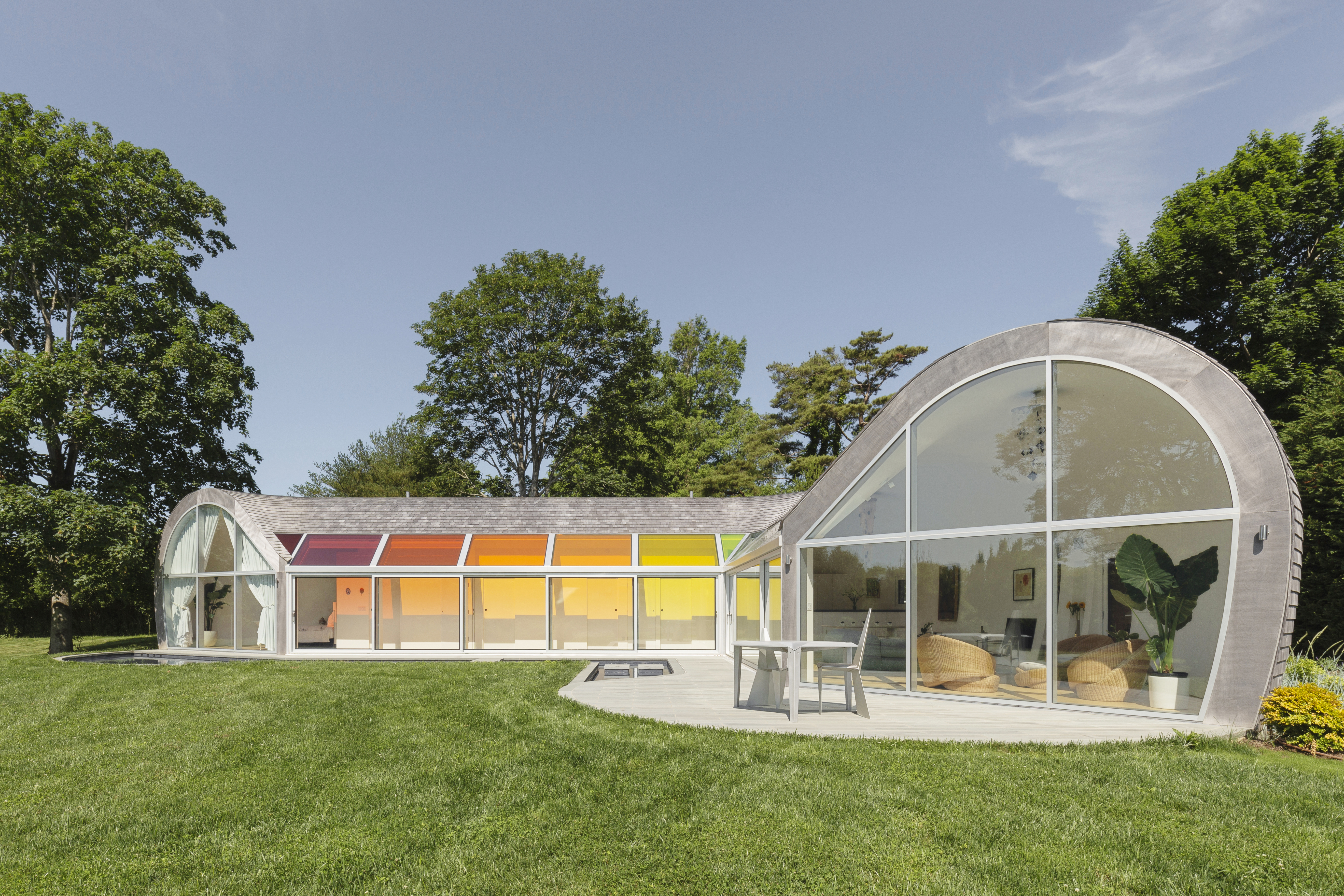 A curving house clad in glass and cedar shingles. A hallway has rainbow colored skylights.