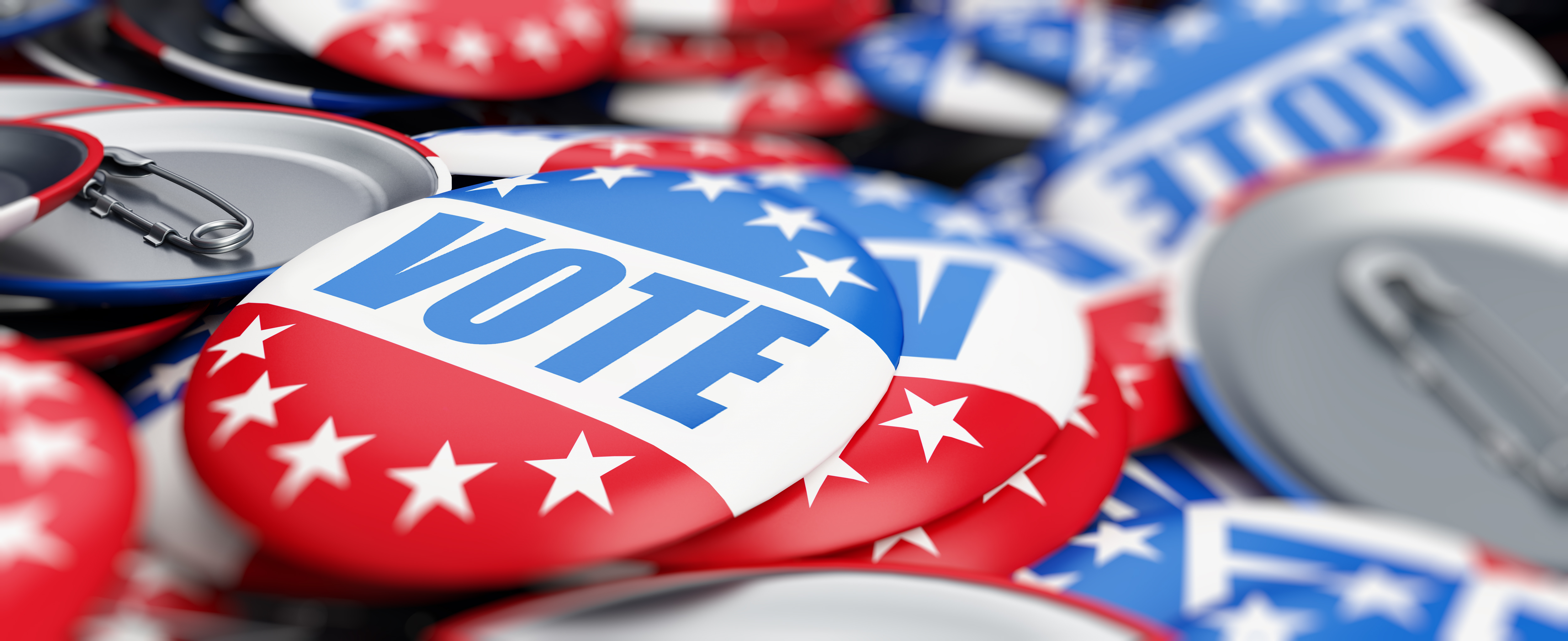 """Pile of round red, white, and blue buttons with stars, reading """"Vote."""""""