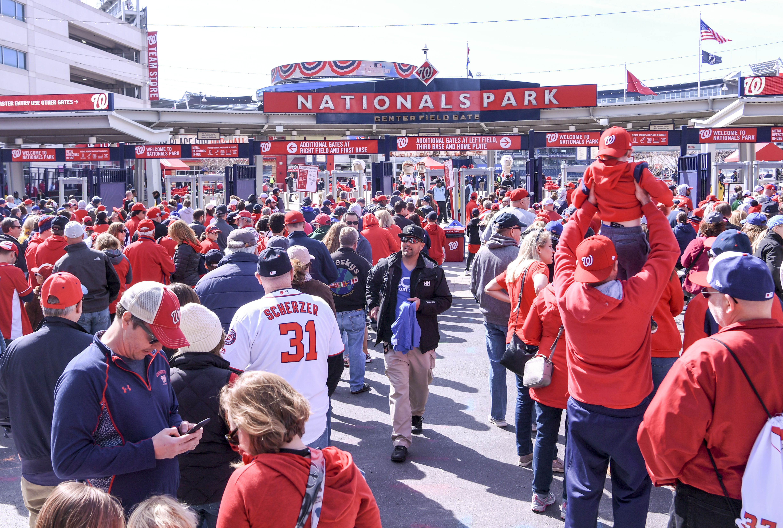 A large group of baseball fans wearing red jerseys wait outside of a baseball stadium on a street.