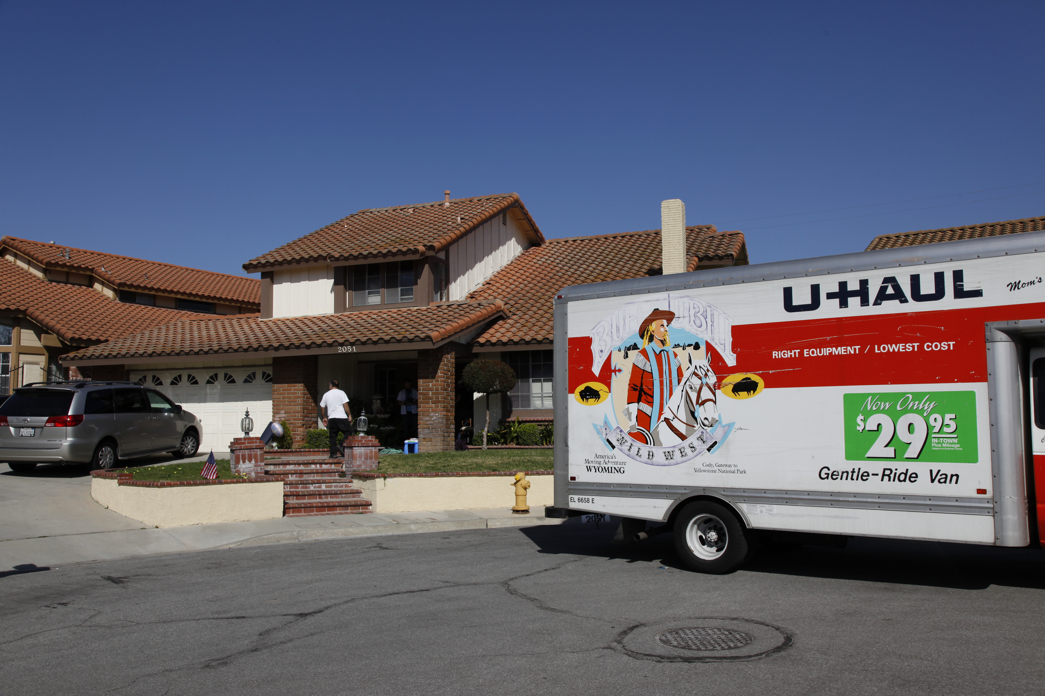 A white home at the end of a cul-de-sac with a Spanish tile roof and a U-Haul trailer parked in the street.