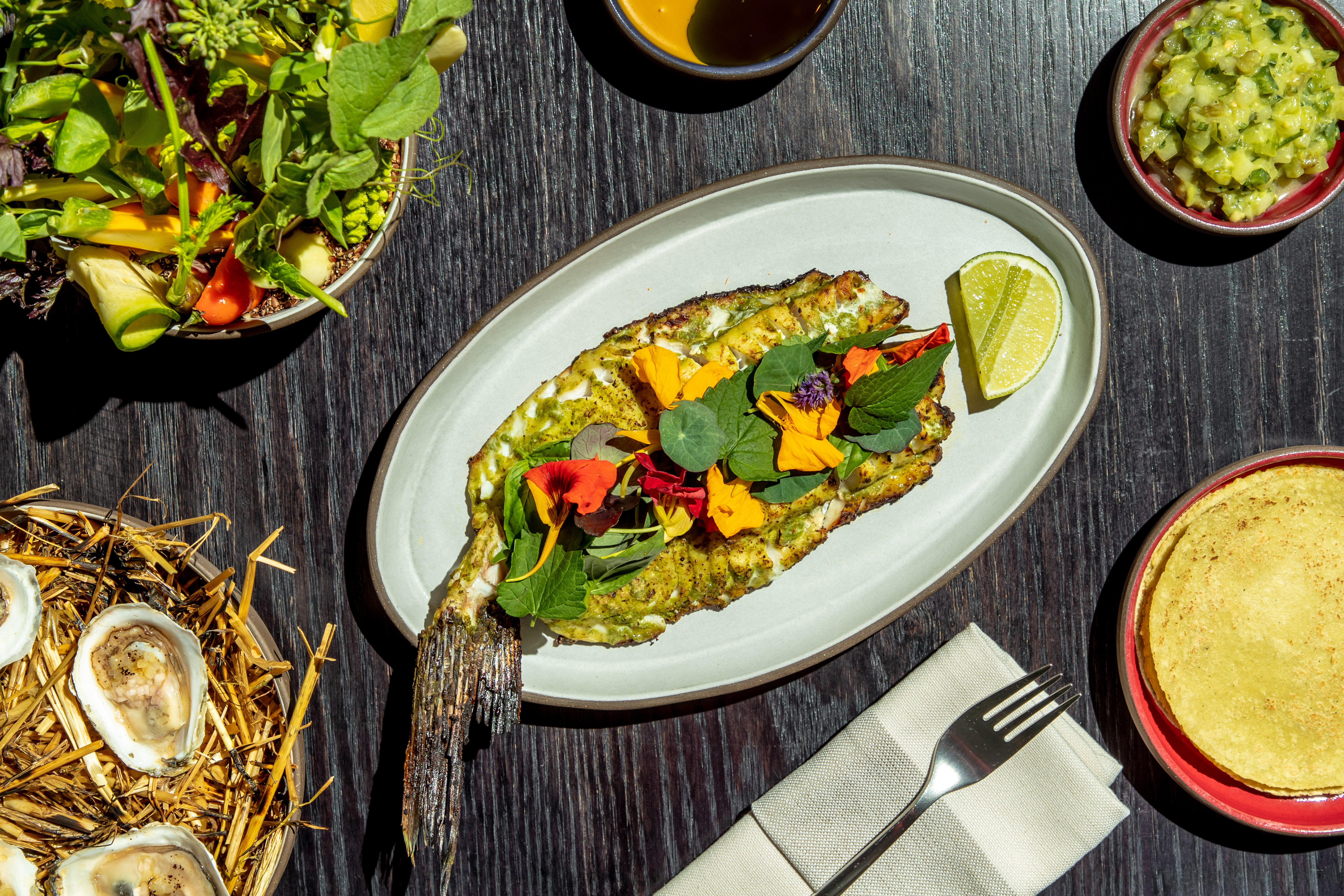 Bass with green salsa and tortillas sit alongside hay-roasted oysters