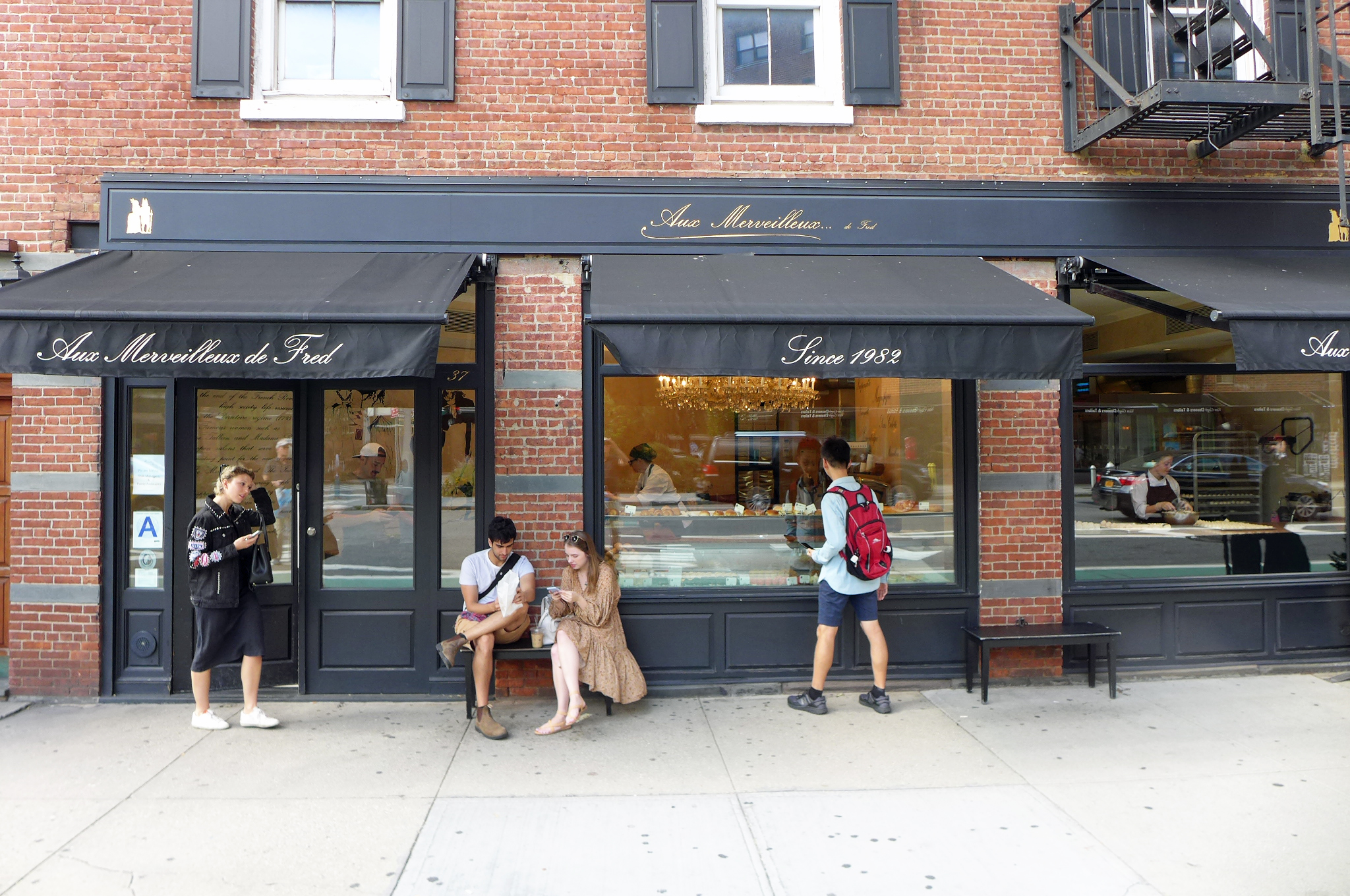 A wide storefront of brick with a window displaying pastries and people milling around outside...