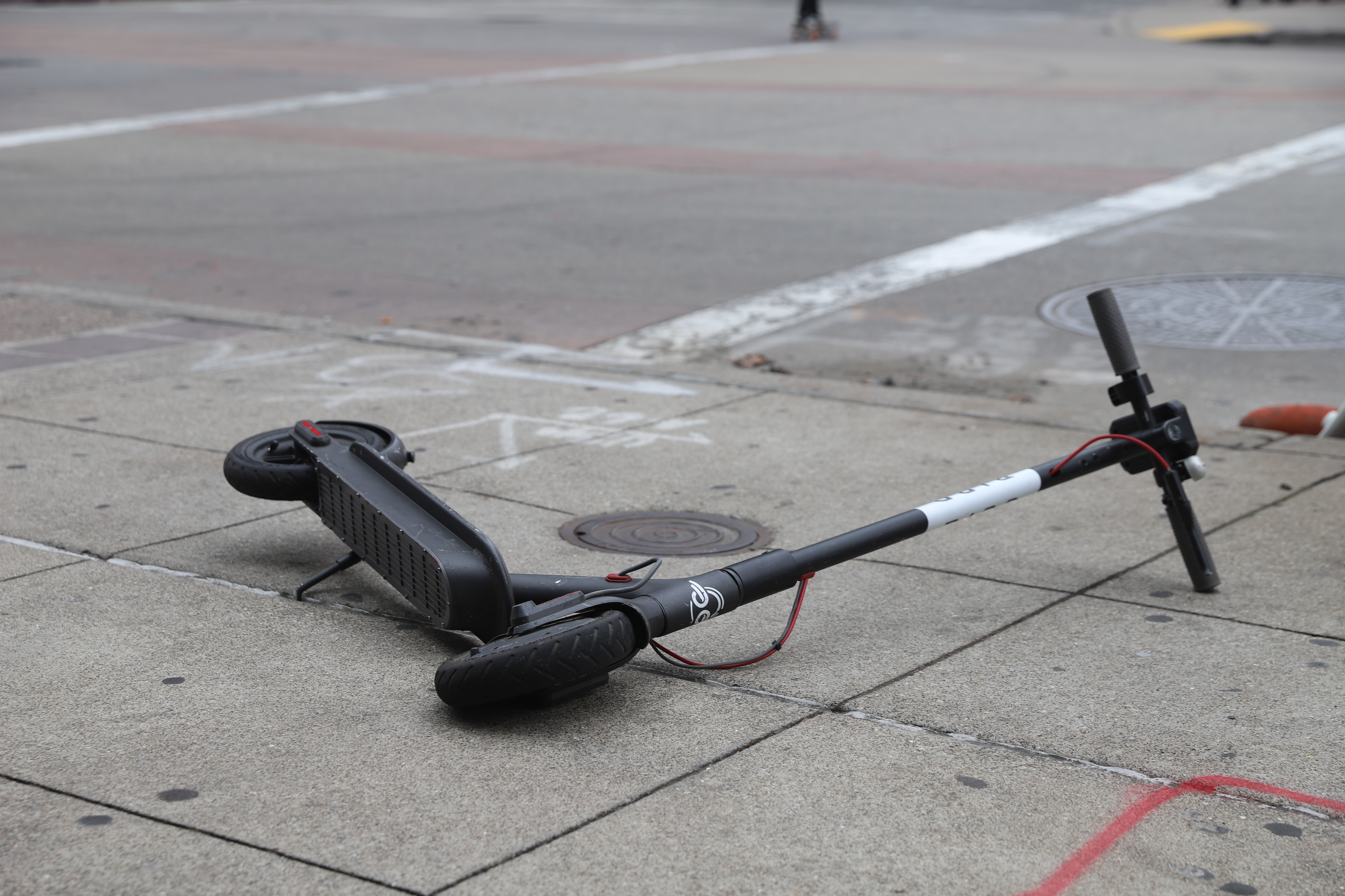A dockless electric scooter on its side on a city sidewalk.