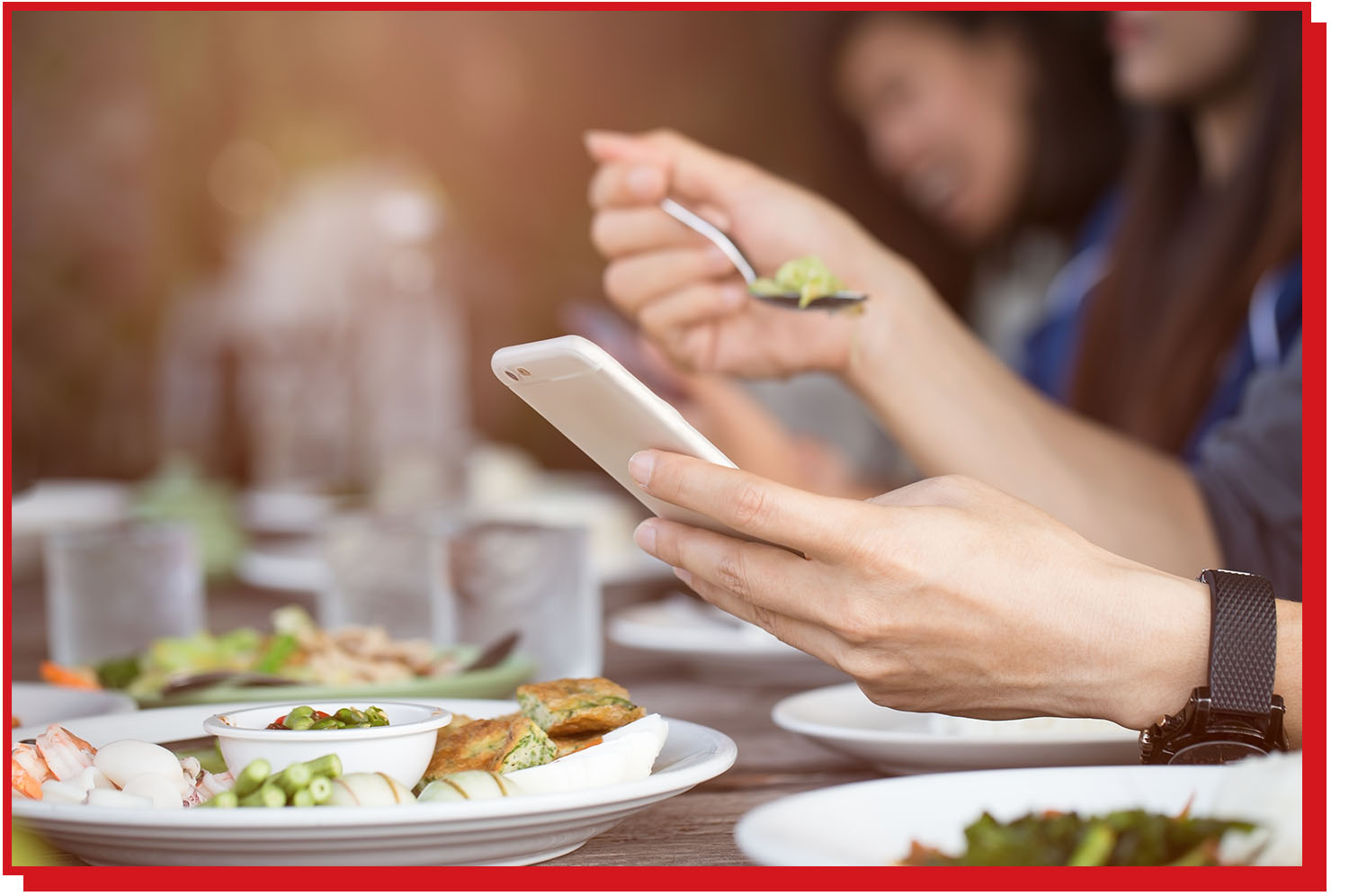 Man reading an article on his phone while sitting at the dinner table.