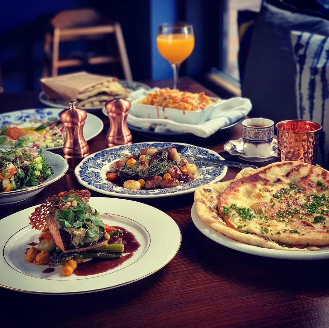 A lineup of homey French dishes arranged on different plates.