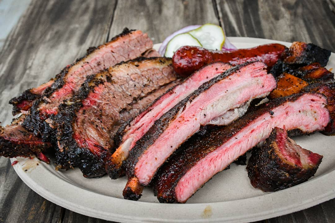 paper plate with brisket, ribs, and meats with barely visible pickles because why vegetables on a wooden picnic table