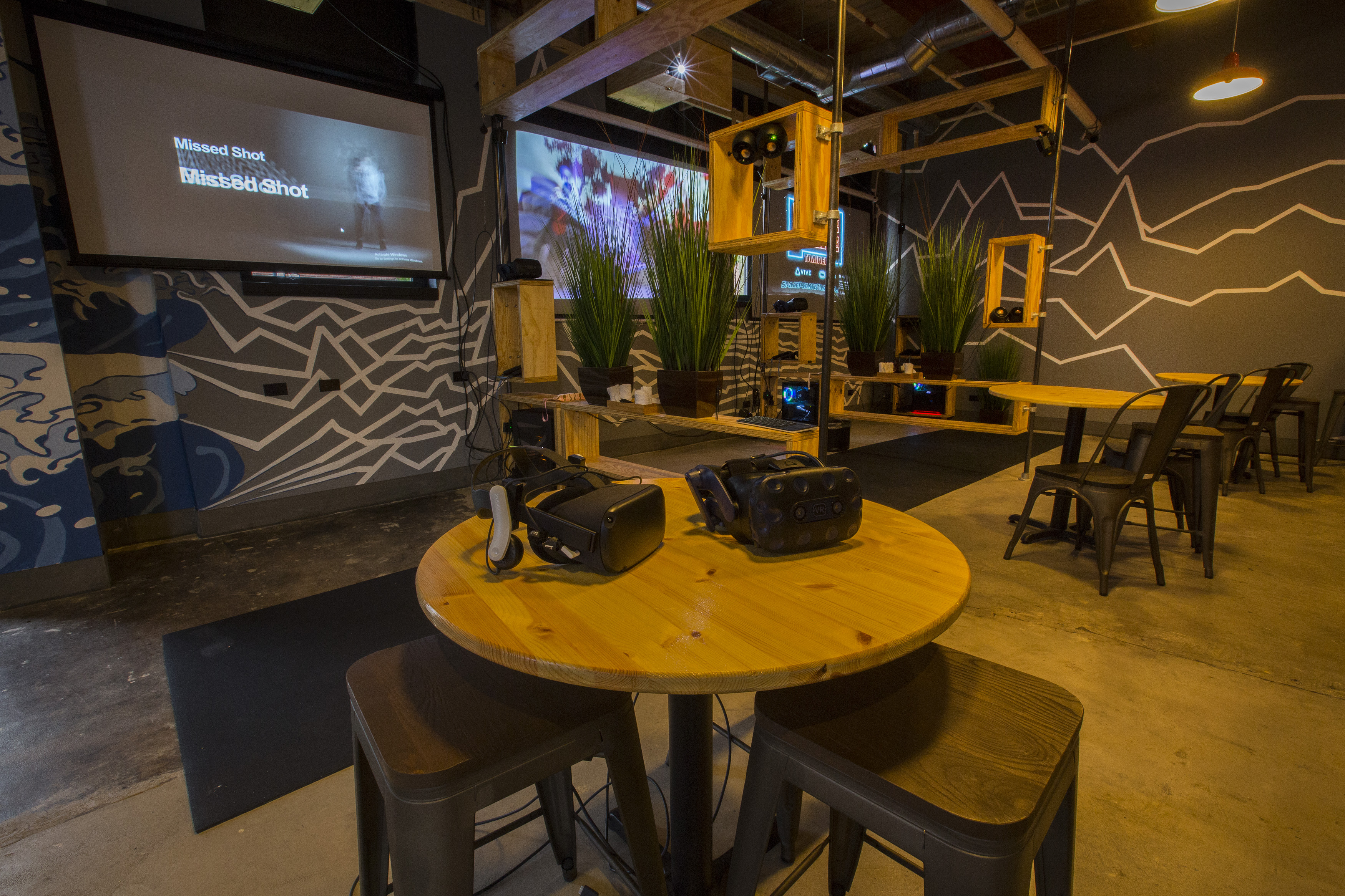 A VR bar with a round table and two headsets and projection screens on the background.