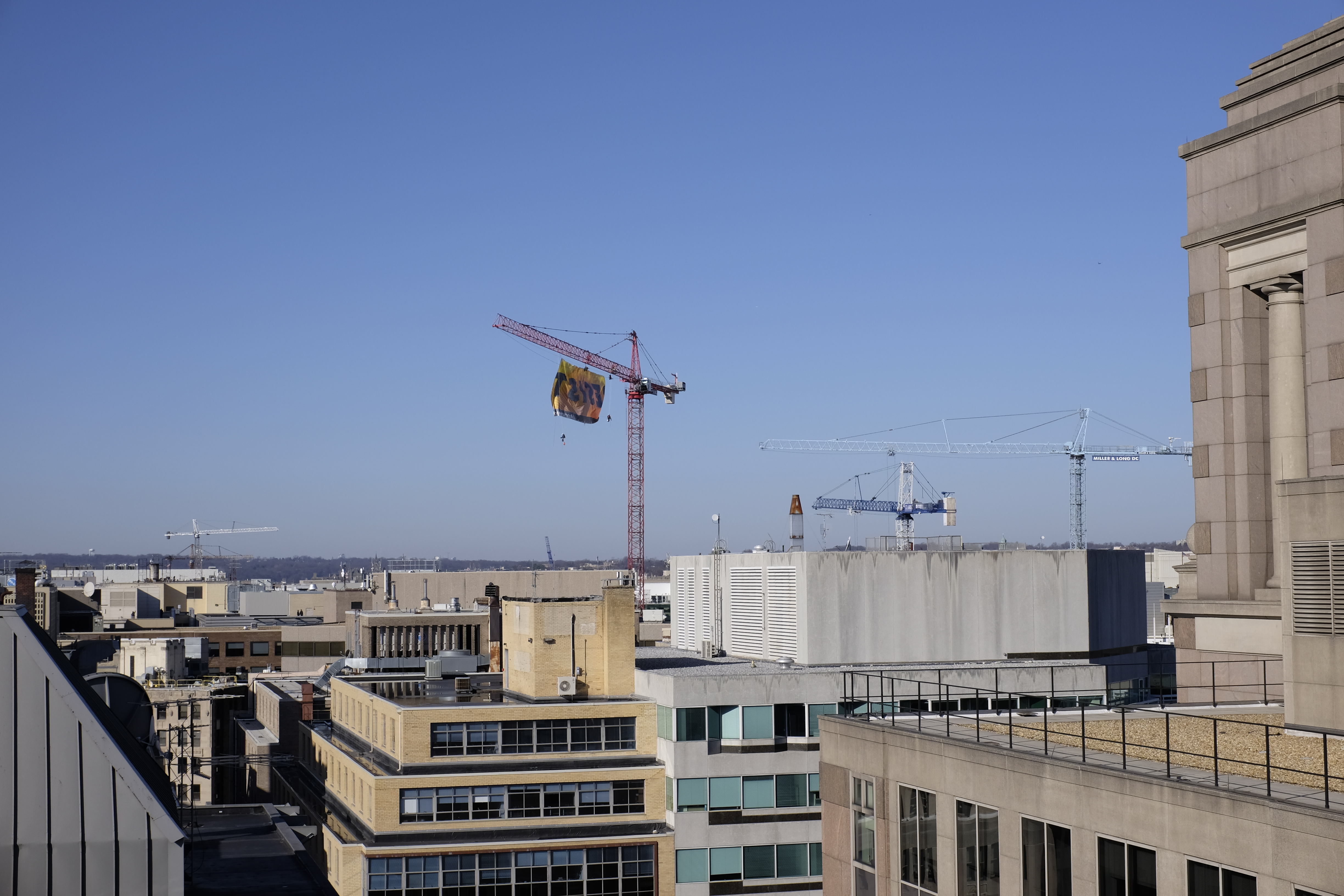 Several cranes are seen in the distance above office buildings from a rooftop.