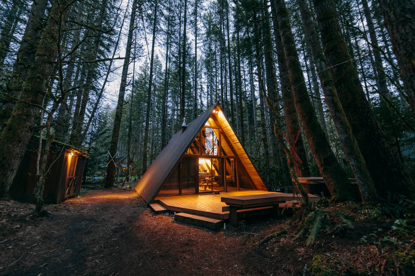 An A-frame cabin with a wide, low front deck at dusk with its lights on, surrounded by evergreen trees.