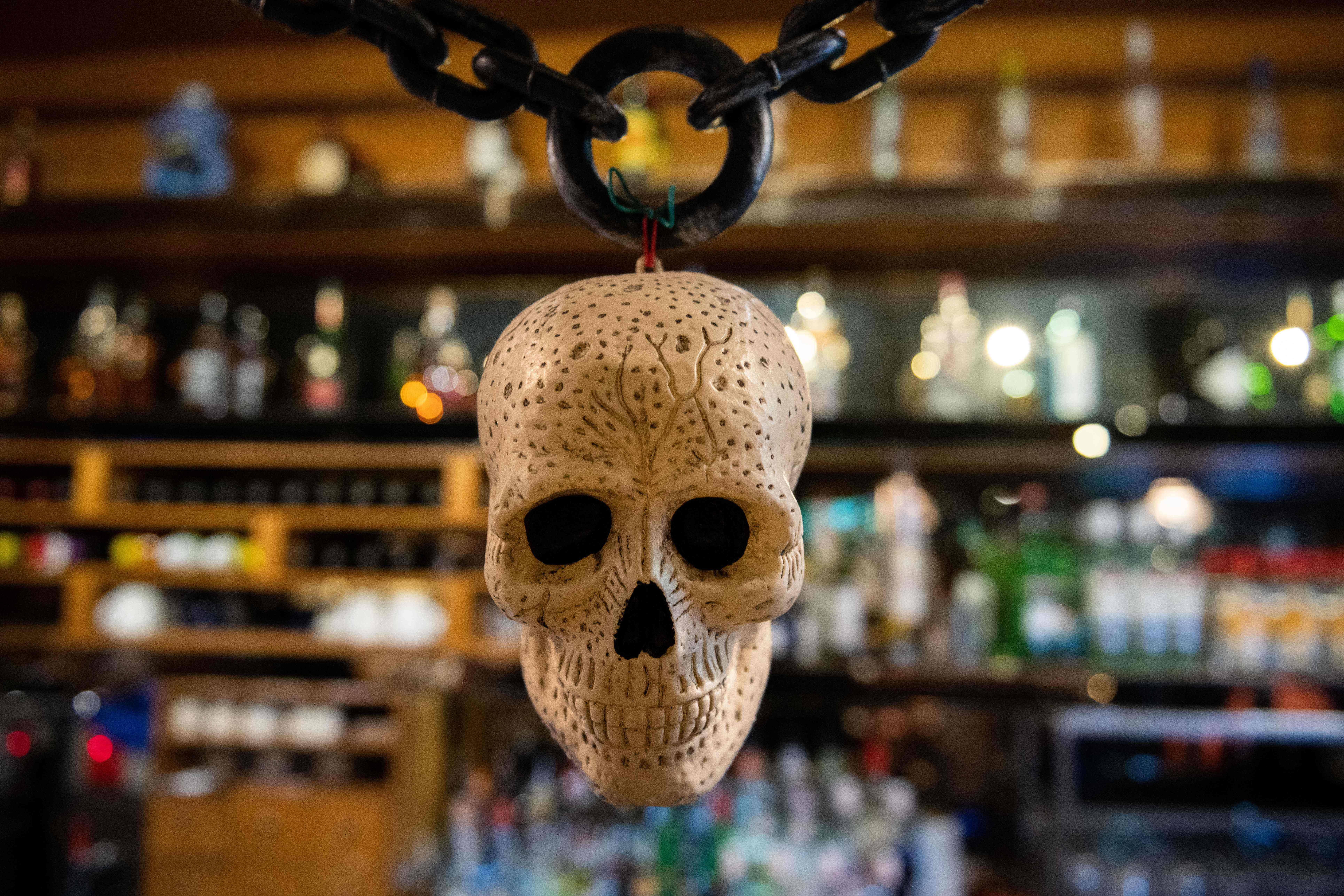 A photo of a skull Halloween decoration is displayed in front of bottles of alcohol at a bar