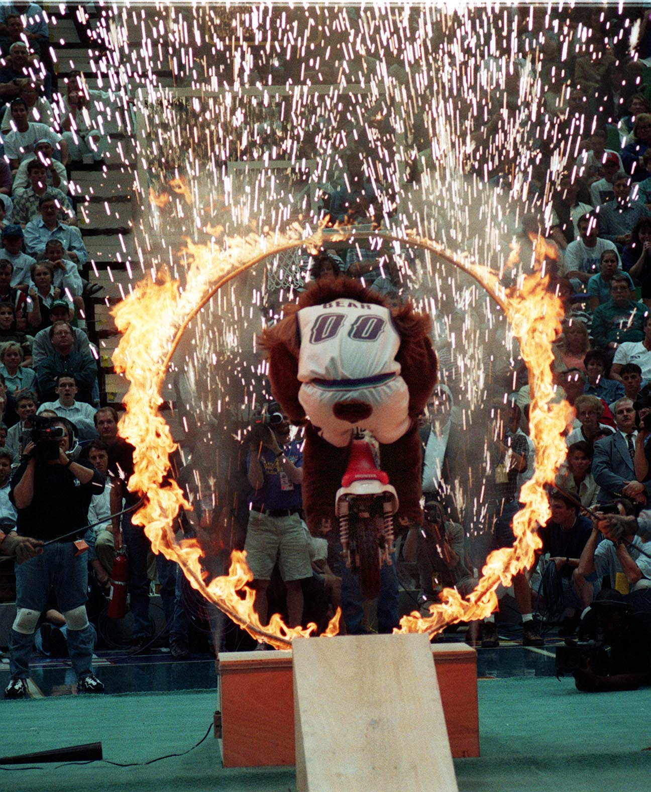 FILE - The Jazz Bear rides a bike through a ring of fire during a break in an NBA game in the Delta Center in Salt Lake City on May 13, 1997.