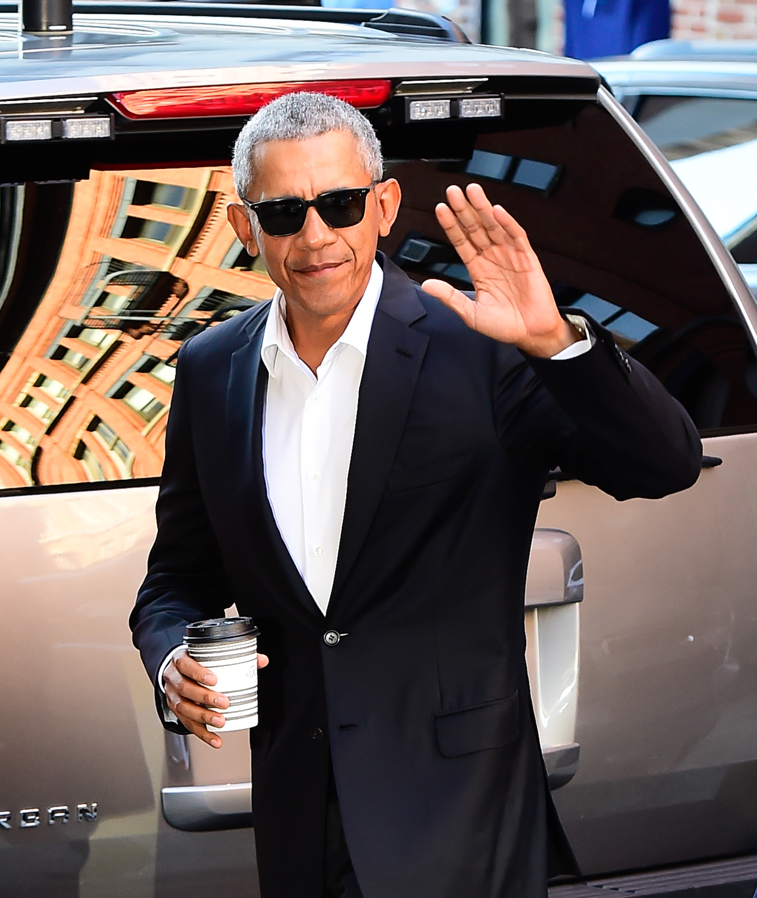 Barack Obama, wearing black sunglasses and a black suit, waves