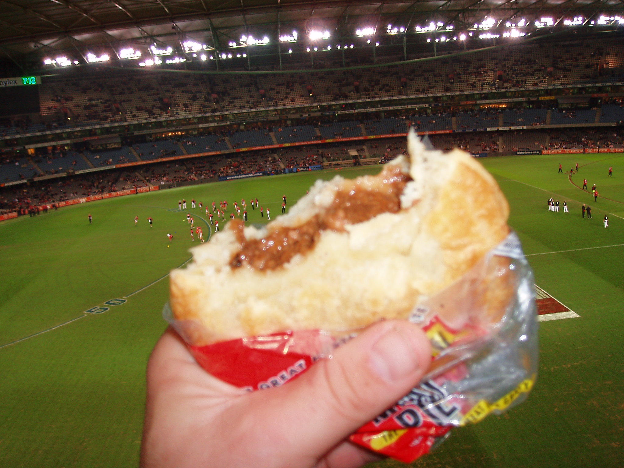 A hand holds a meat pie in a sports stadium