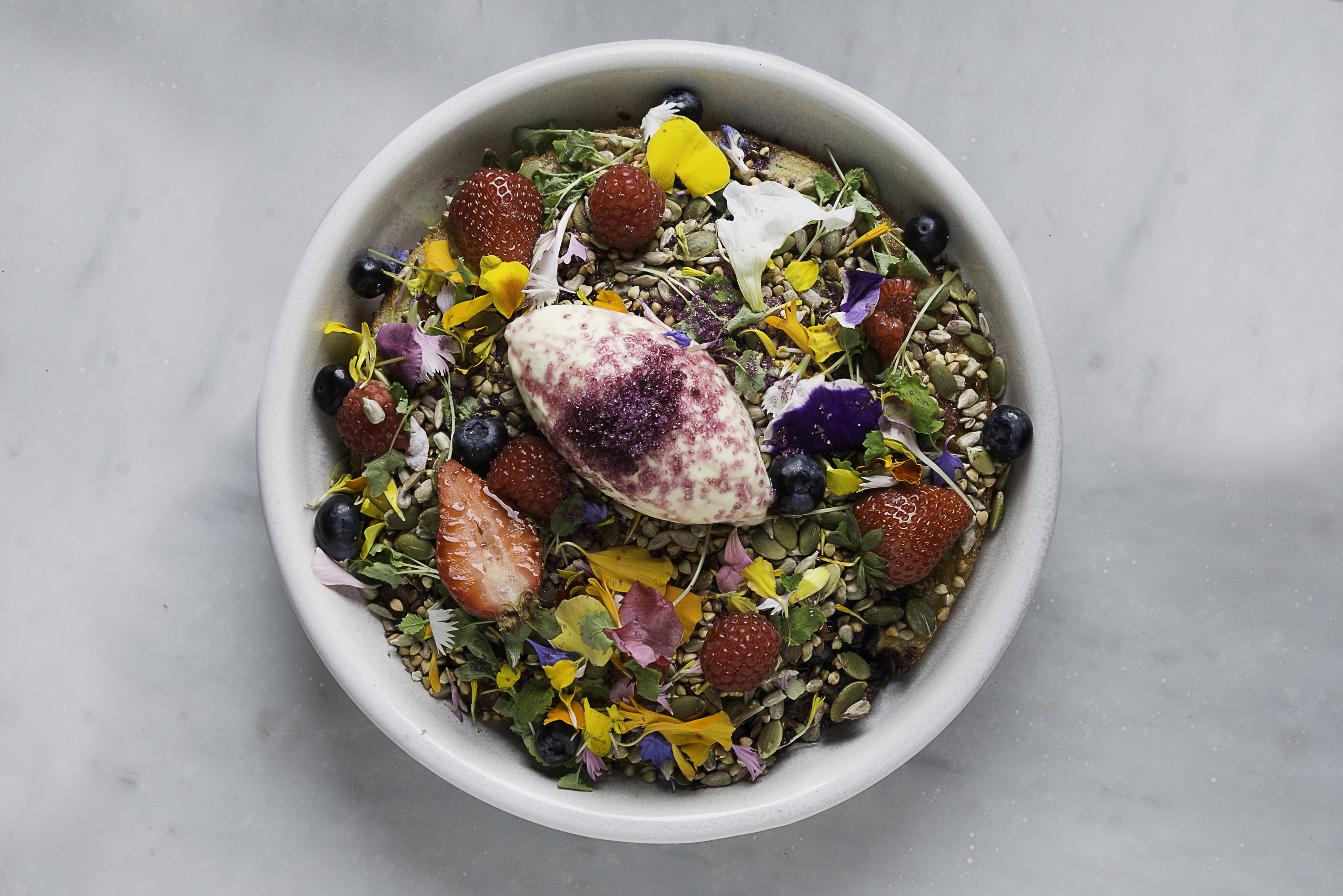 On a marble countertop, a bowl is filled with a hotcake topped with seeds, flowers, sliced strawberries and a dollop of cream