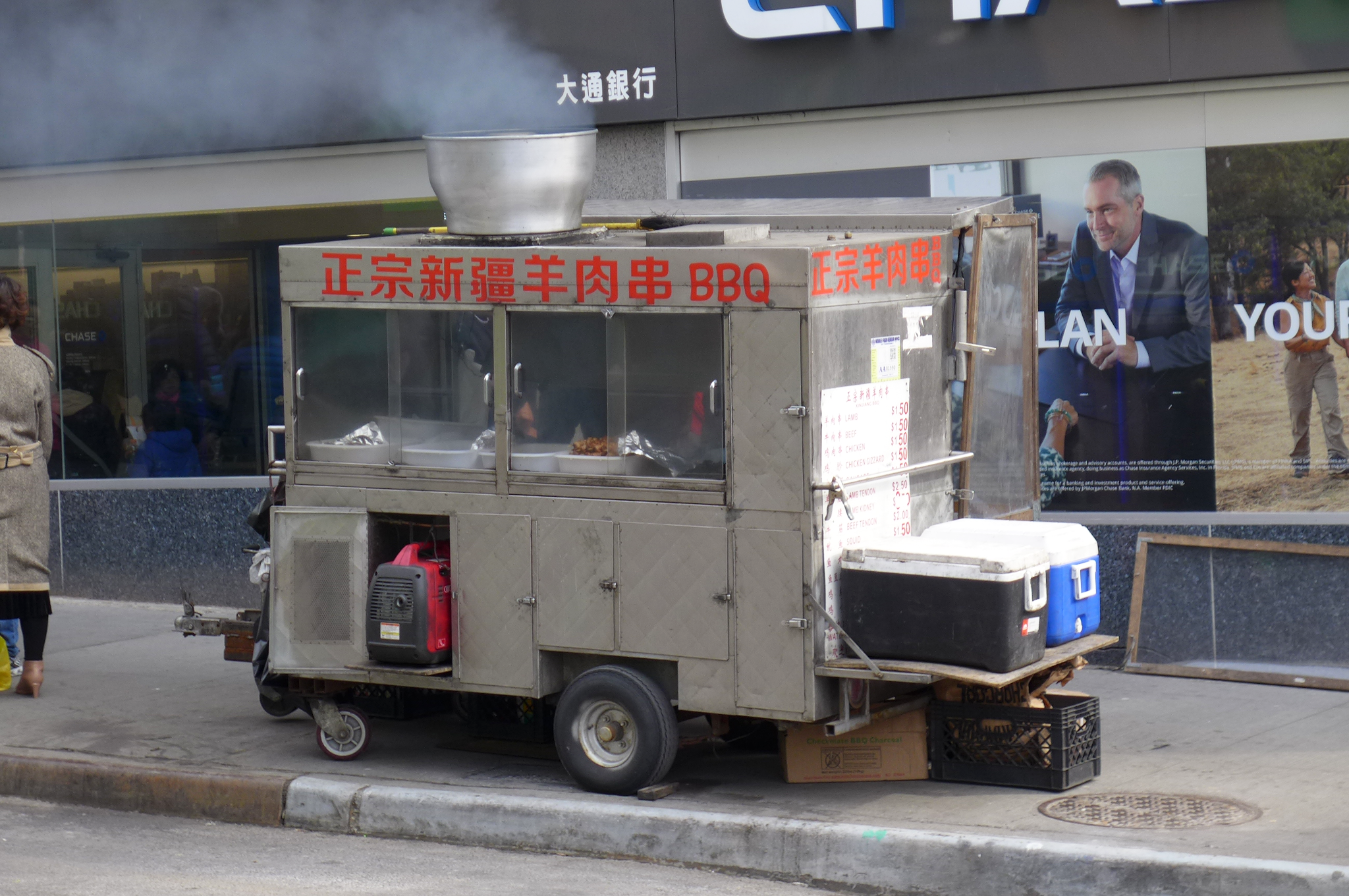 A metal food cart on the sidewalk with steam coming out the top