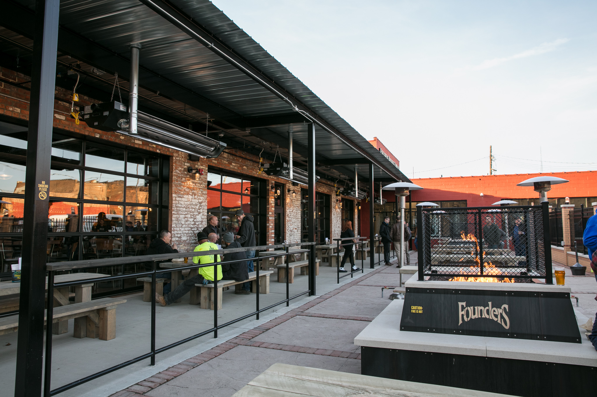 The patio at Founders in Detroit features a firepit with the logo on it.