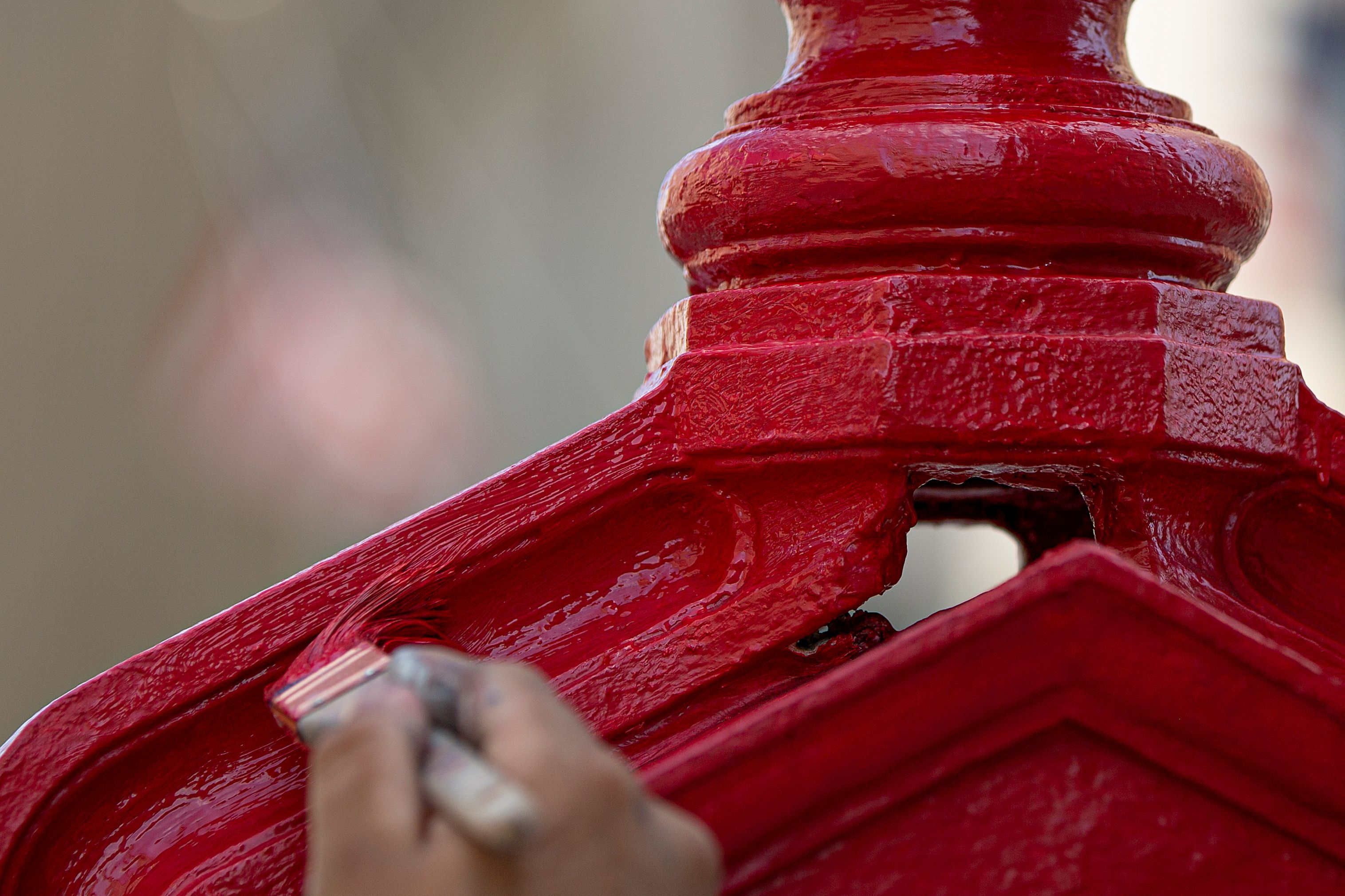 A hand is shown painting an old call box for emergency responders with red paint.