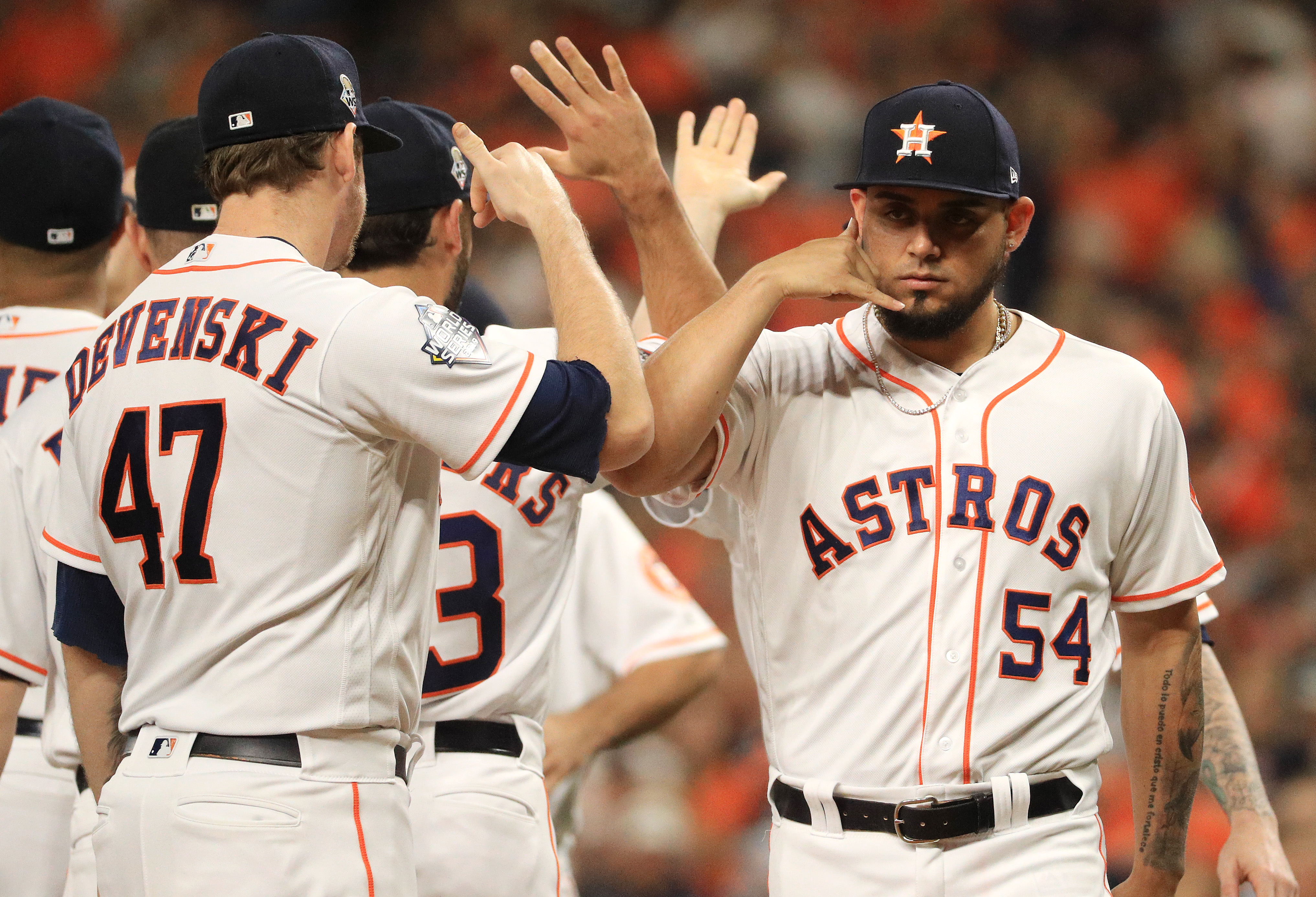 Roberto Osuna (number 54) of the Houston Astros baseball team high-fives his teammates on the field.