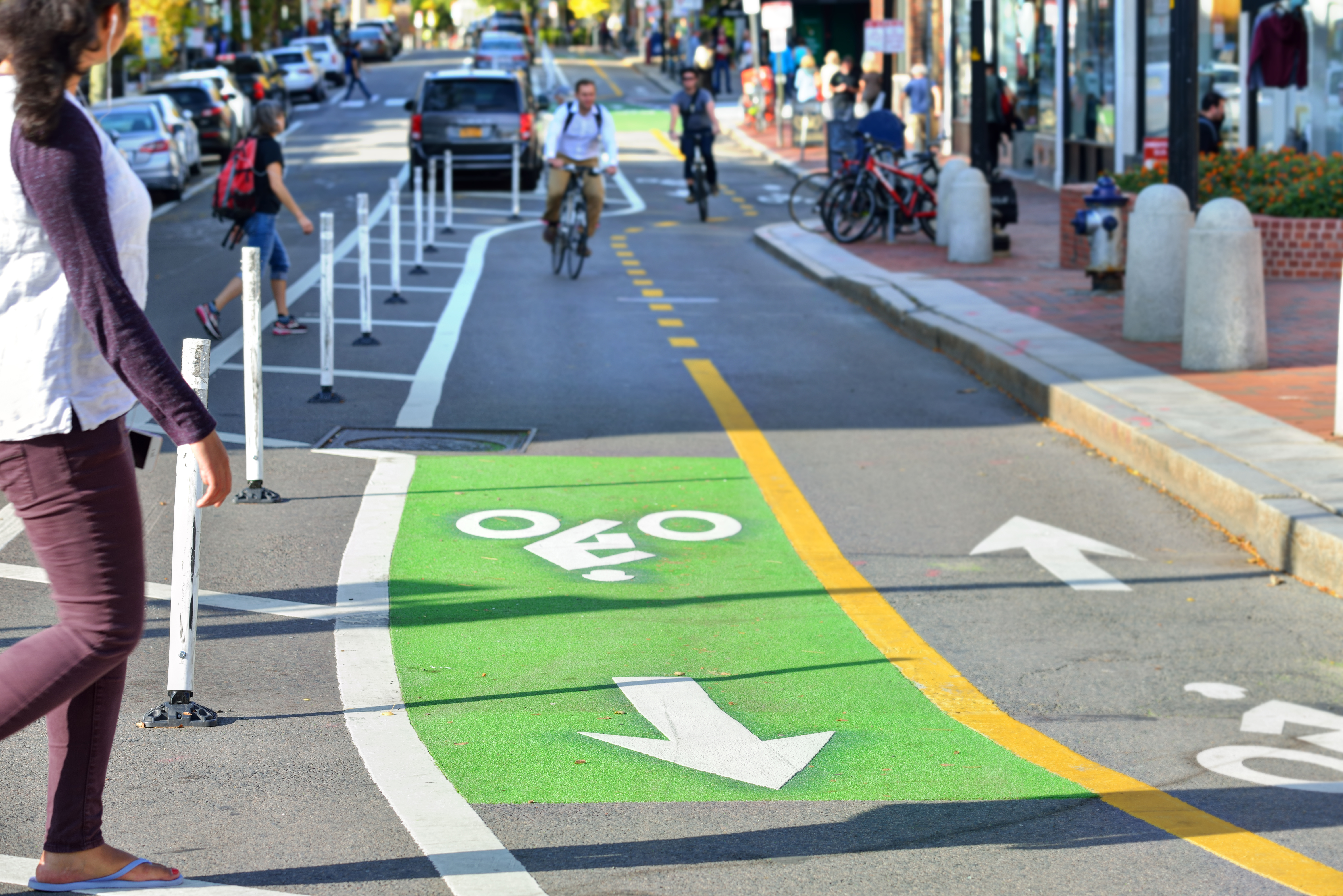 Two-way protected bike lanes with pavement markers, striped median, buffer zone and flexible delineators in city street.