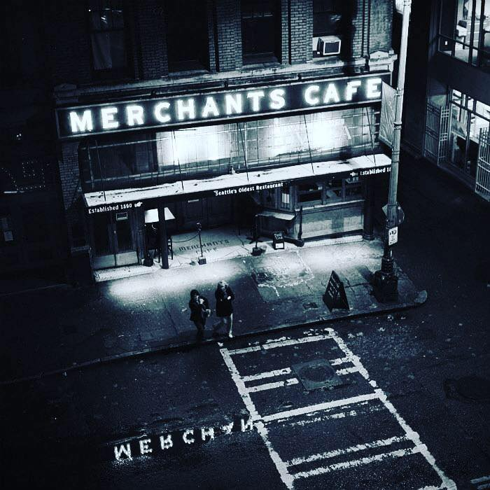 A black-and-white photo of the exterior of Merchant's Cafe, with the restaurant's iconic sign lit up at night.