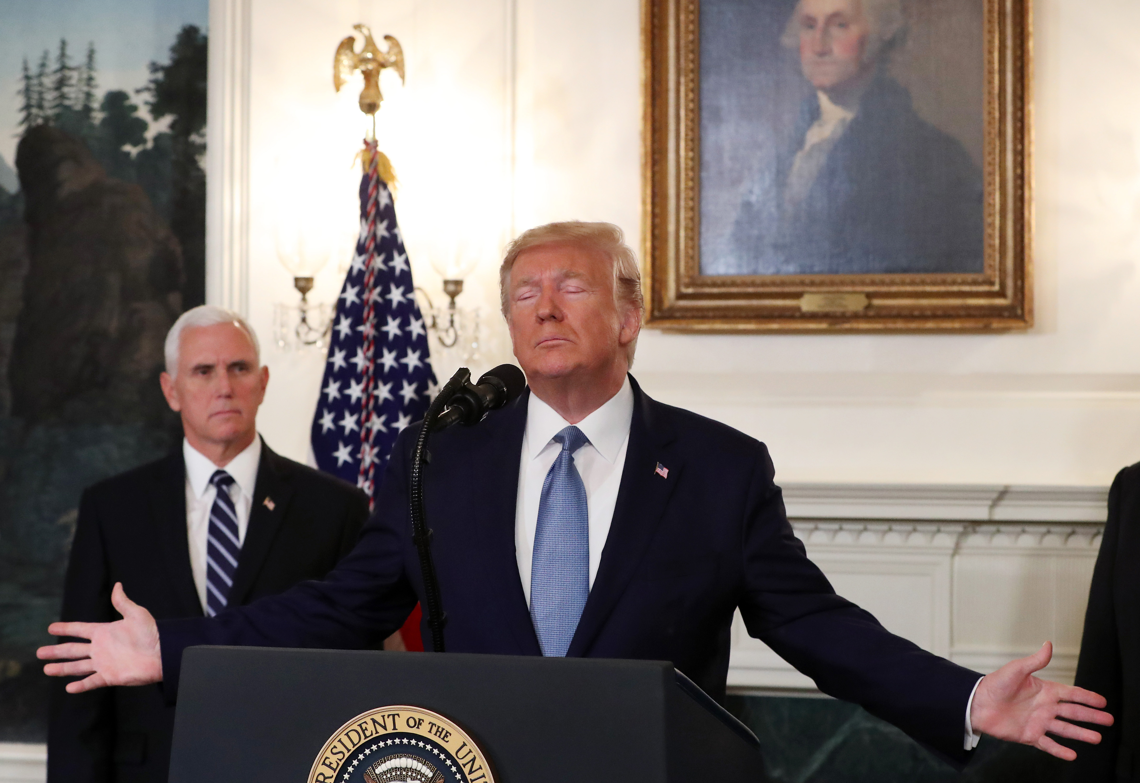 President Donald Trump stands with his eyes closed and his arms spread out at the podium with Vice President Mike Pence behind him at the White House.