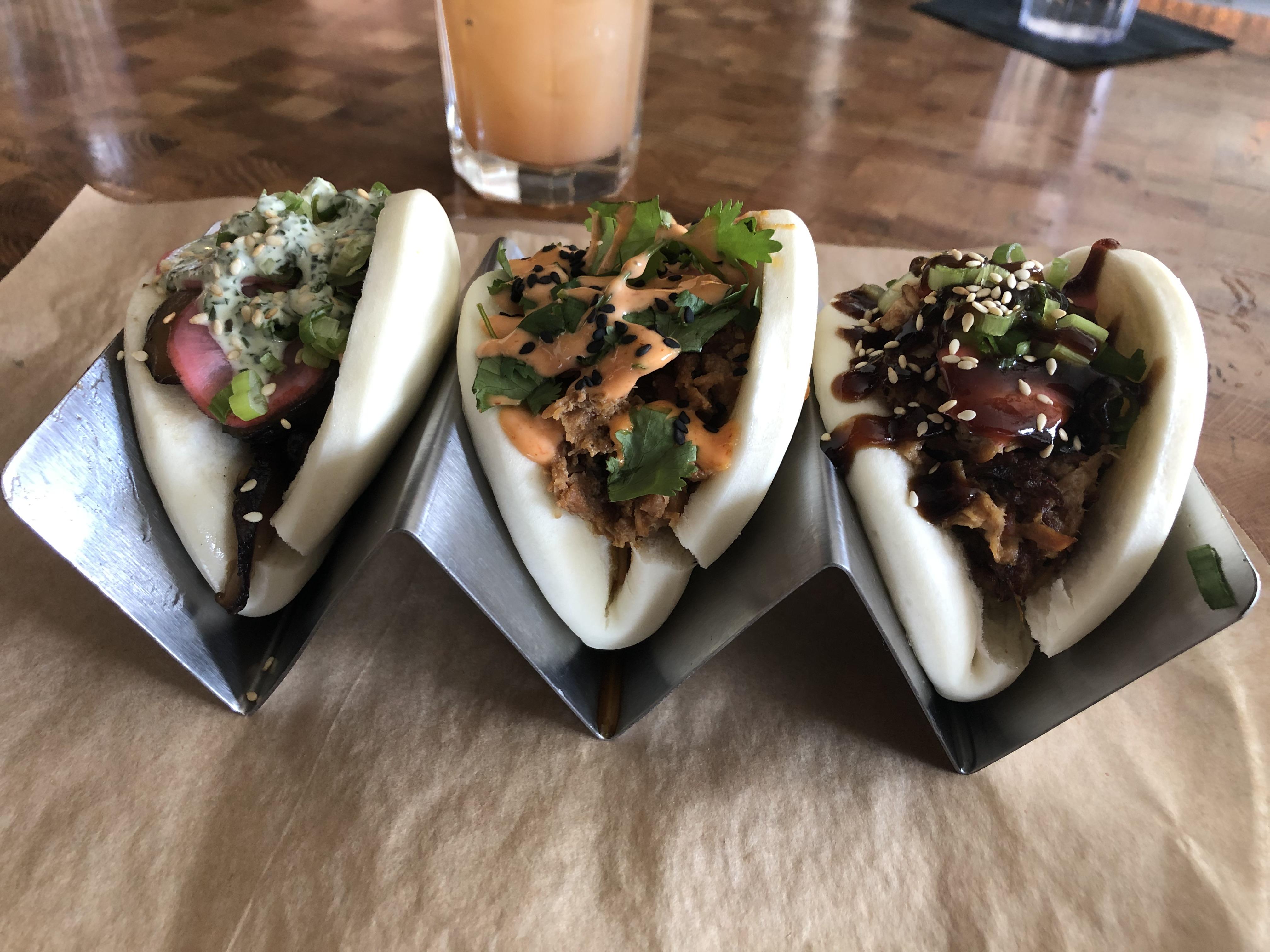 A photo of a trey containing Meta Asian Kitchen's shiitake mushroom (left), pork (center) and chicken bao buns