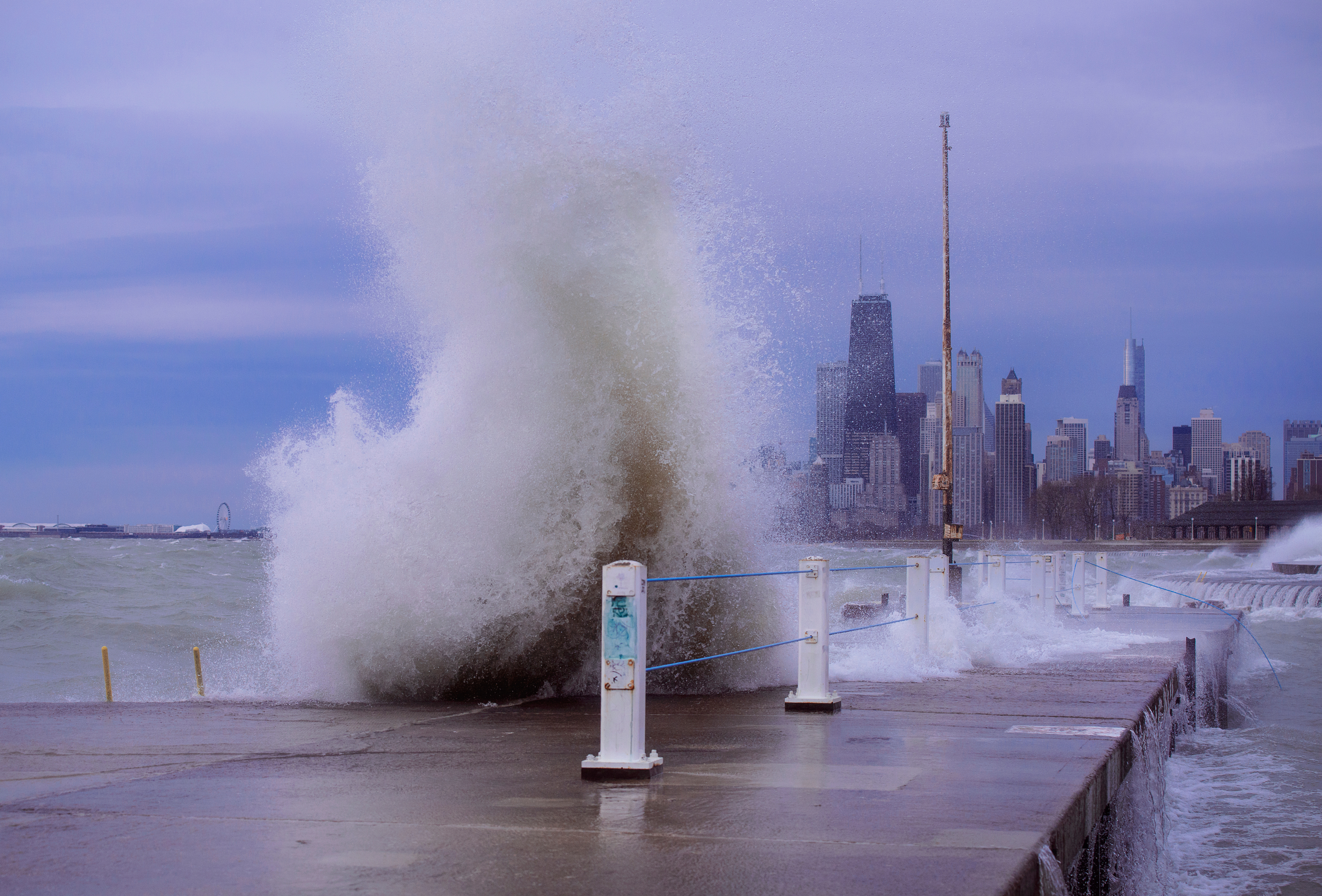 A large wave breaks over a concrete and metal pier next to a body of water. A row of tall buildings rises in the distance.