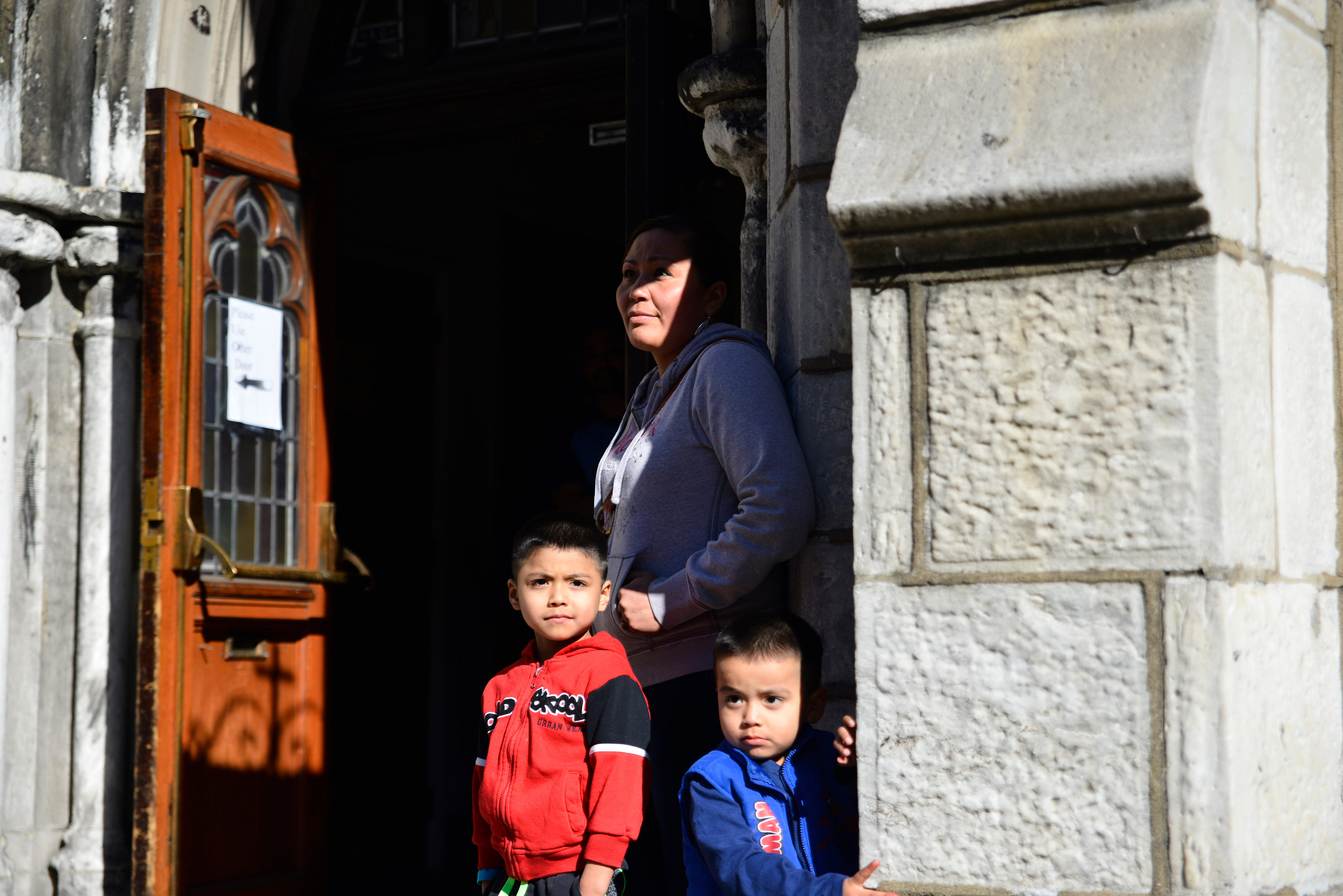 A woman and two young children stand in the doorway of a church.