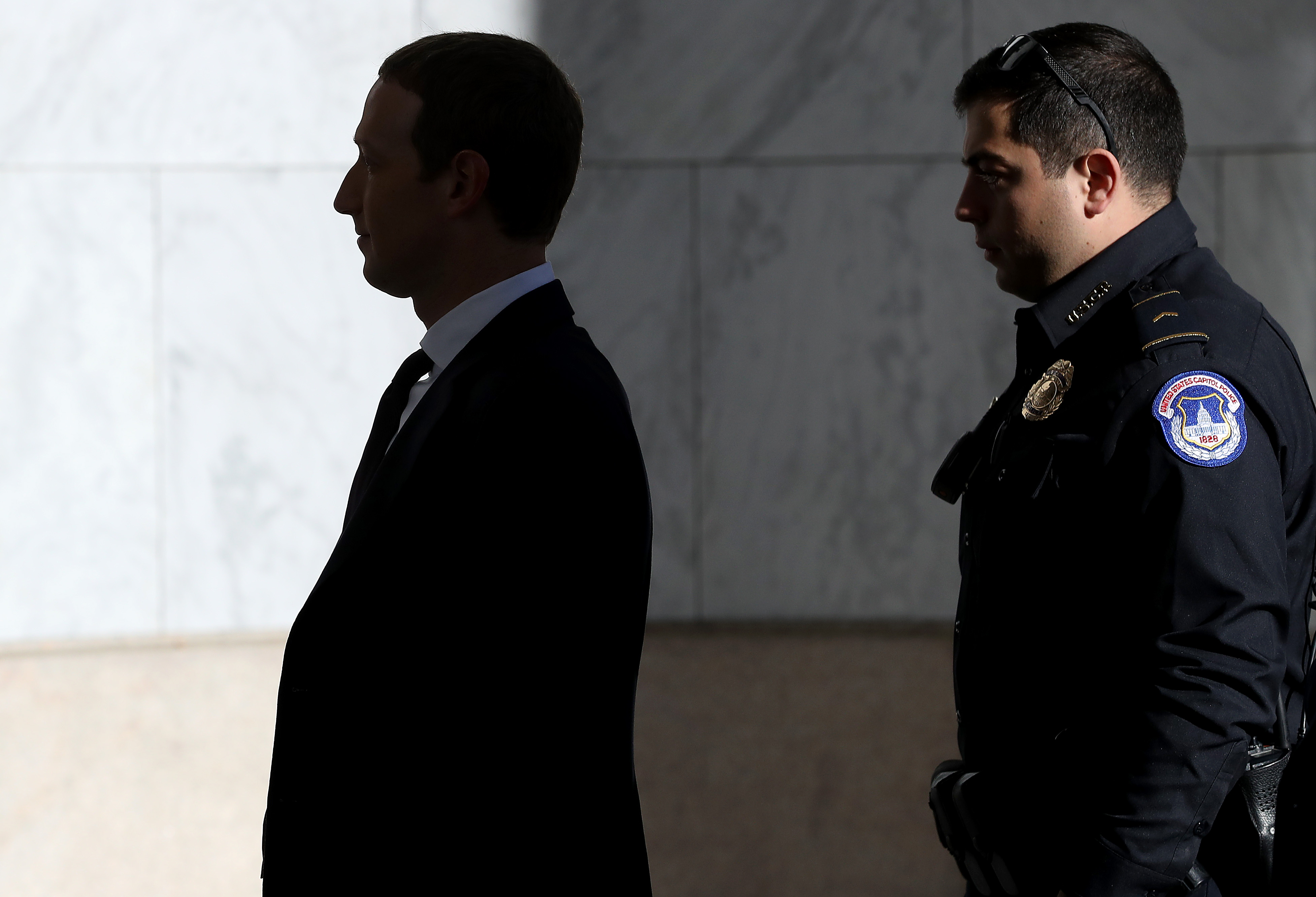 Mark Zuckerberg walking into Congress followed by a security official.
