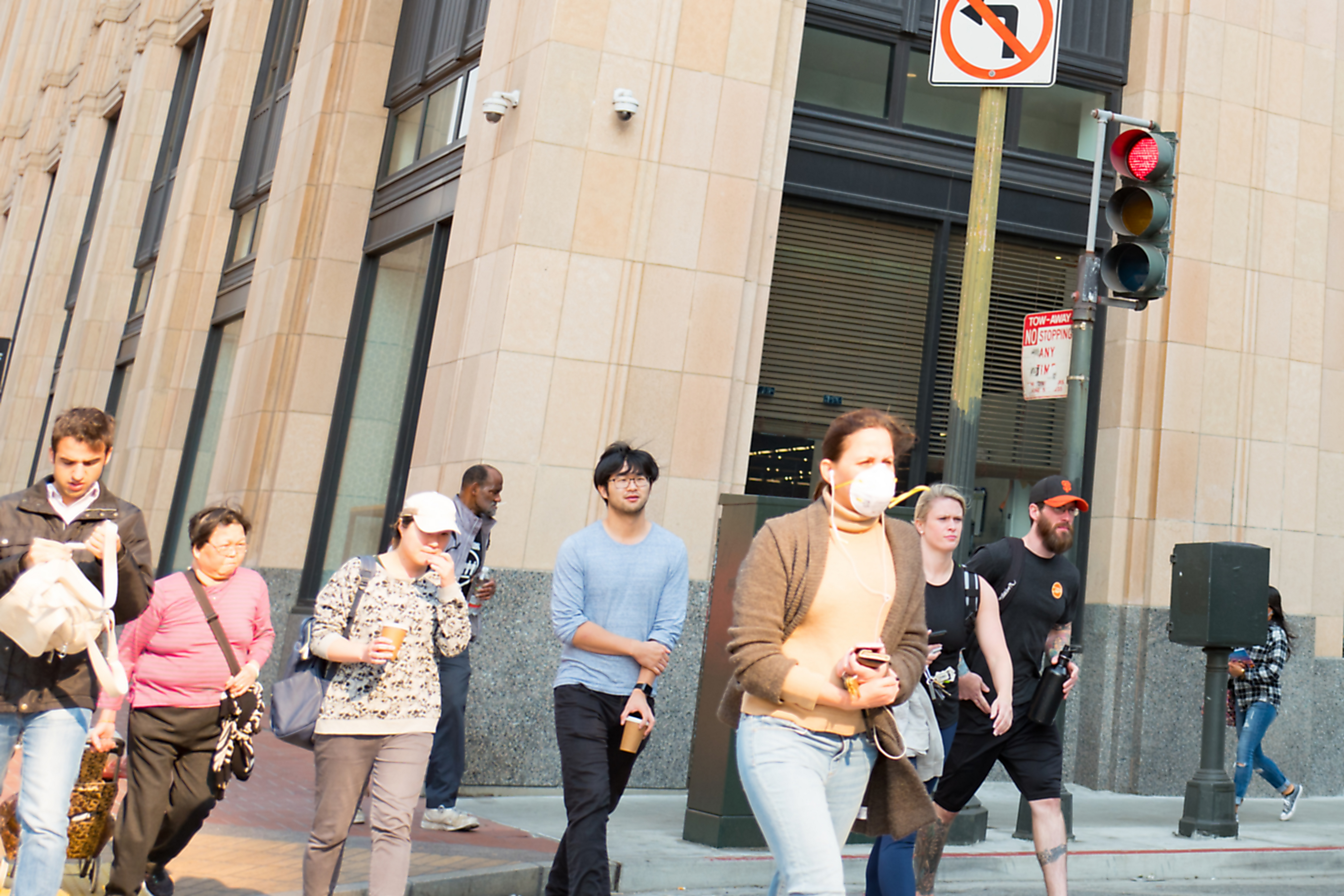 A person wearing a breathing mask walks across a street with three other people.