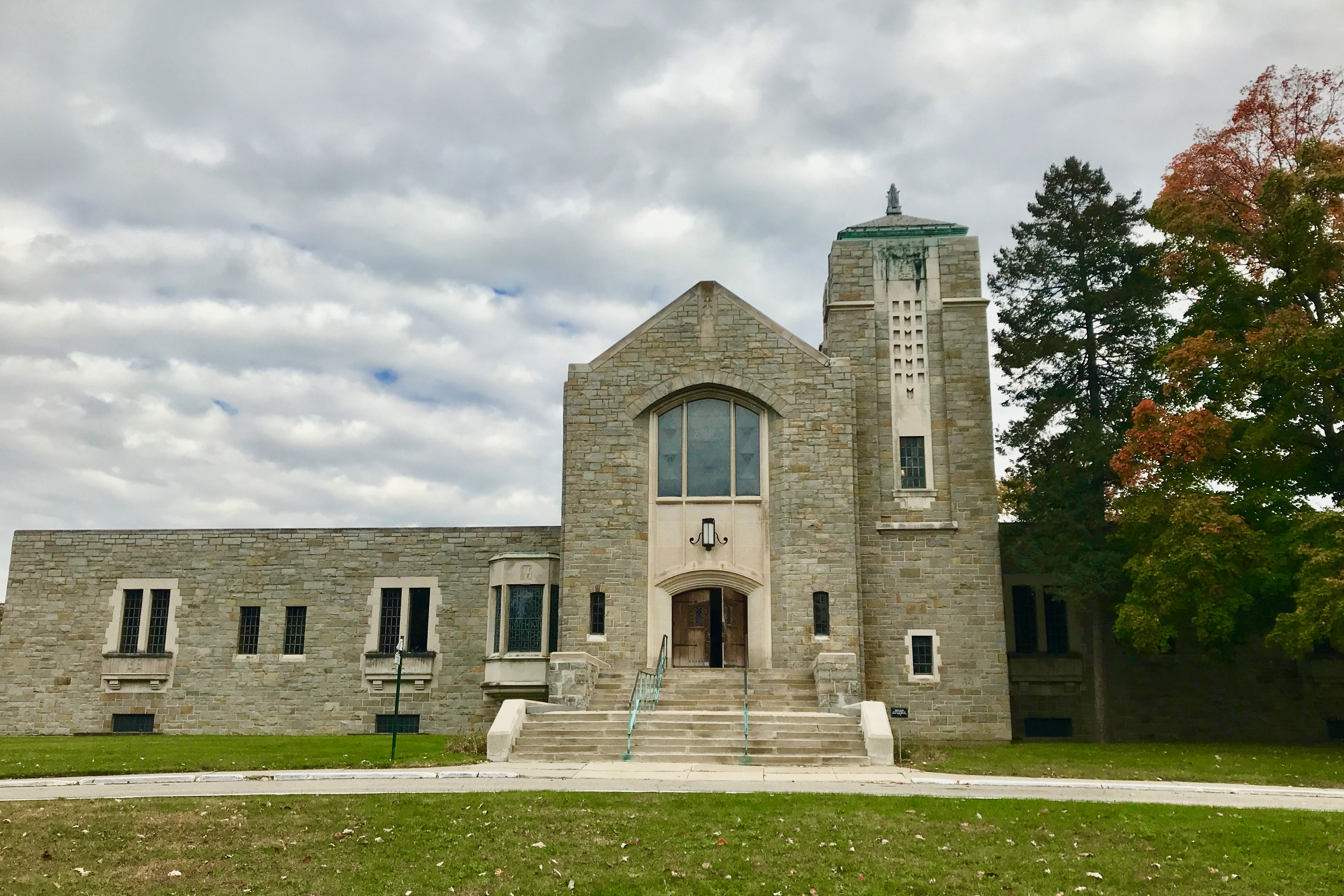 A stone, church-like building in front of a green lawn. There's a steeple to the right of the entrance.