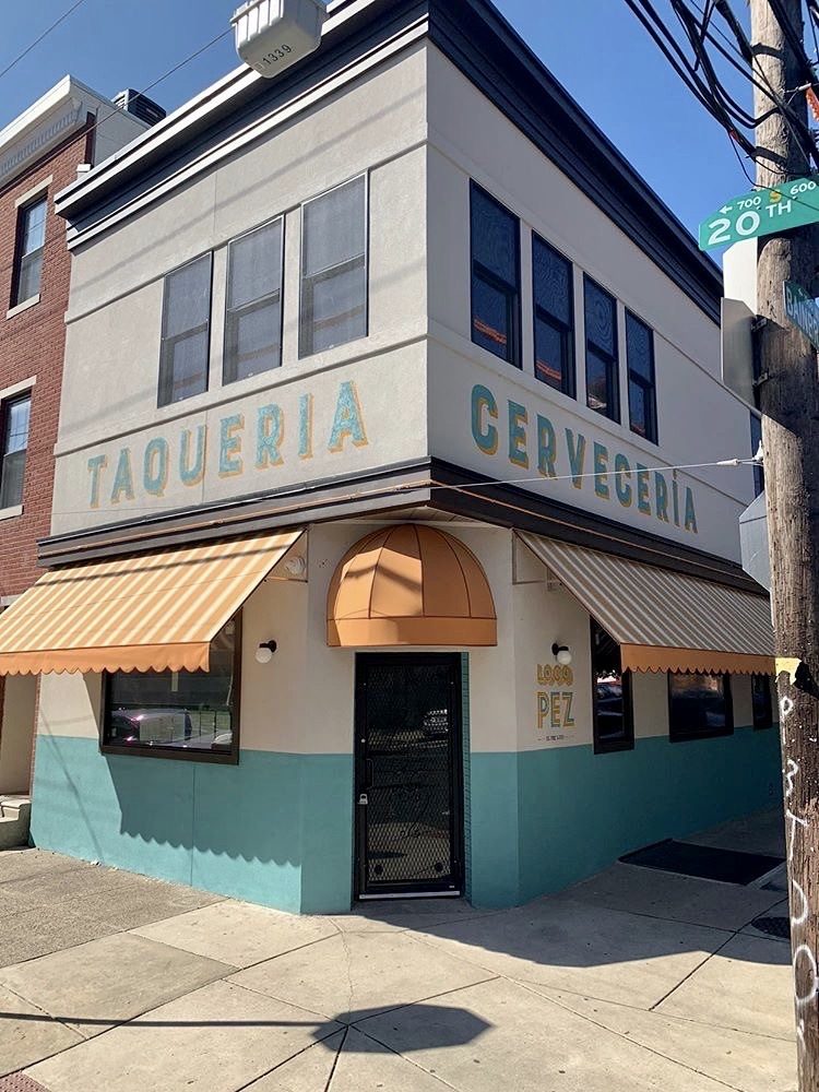 corner building with orange awnings and sign that says taqueria and ceveceria