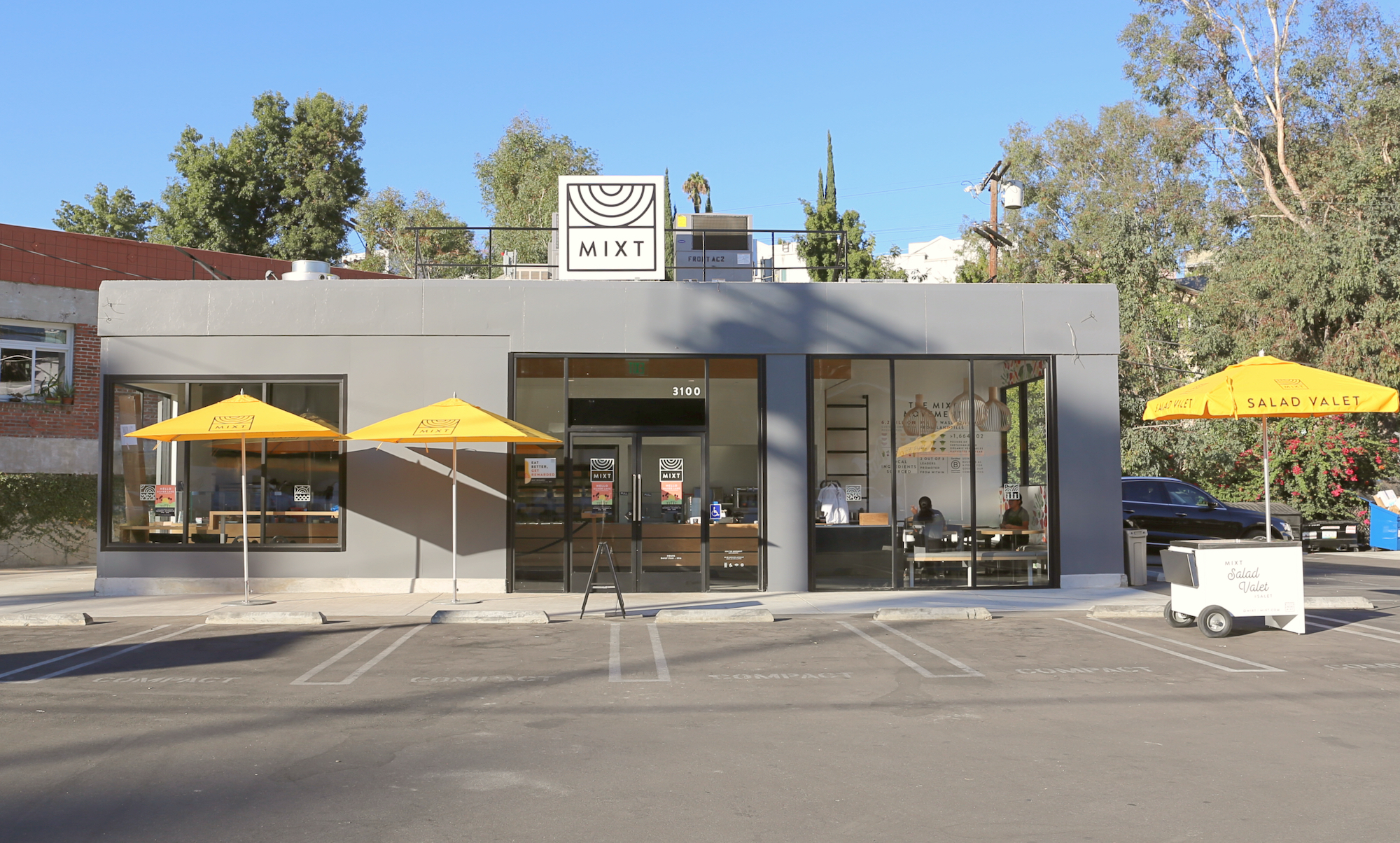 A finished restaurant space with yellow sun shades out front.