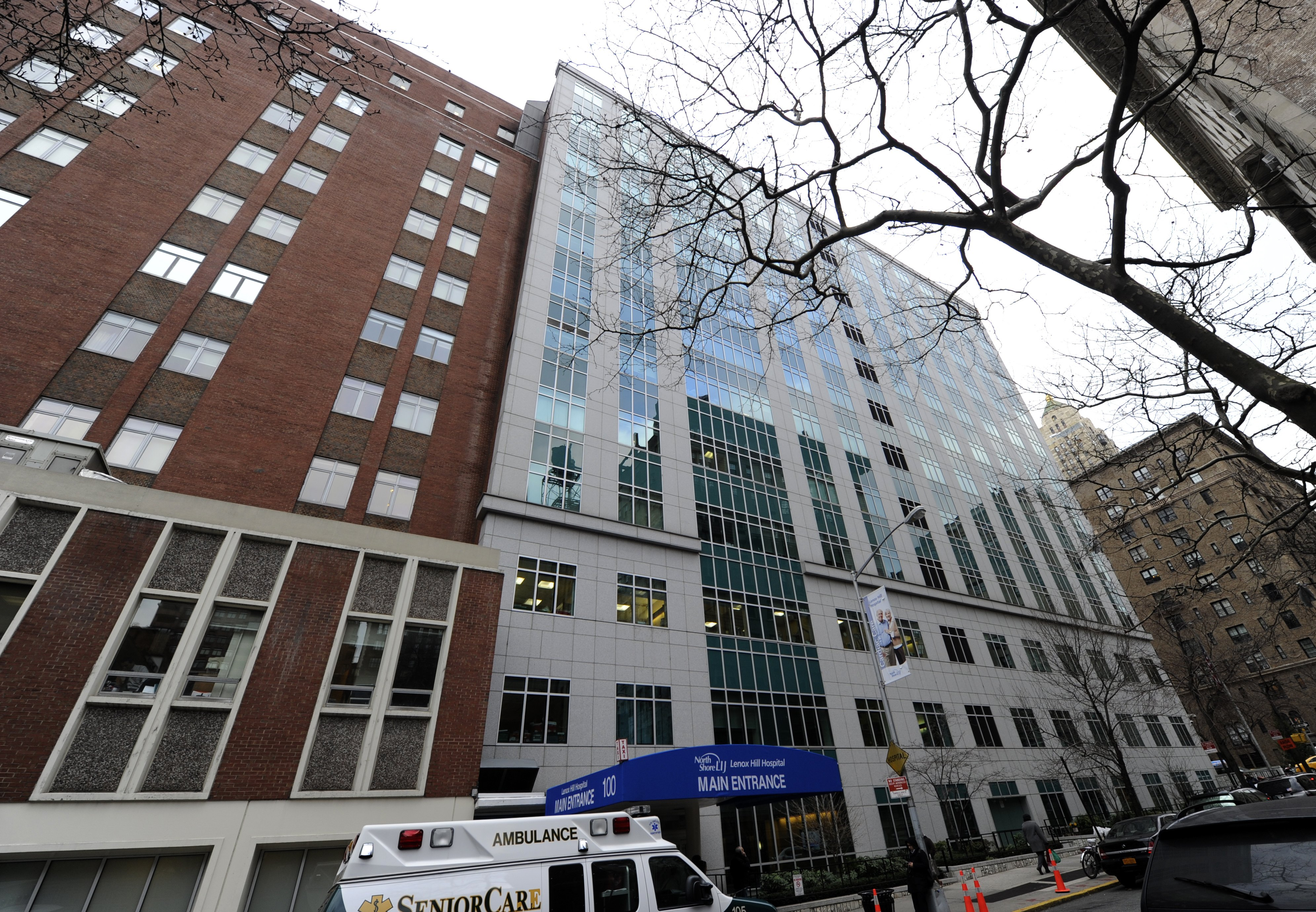 A view of a grey and brick hospital building on an Upper East Side block with a white and gold ambulance parked outside of an entrance with a blue awning.