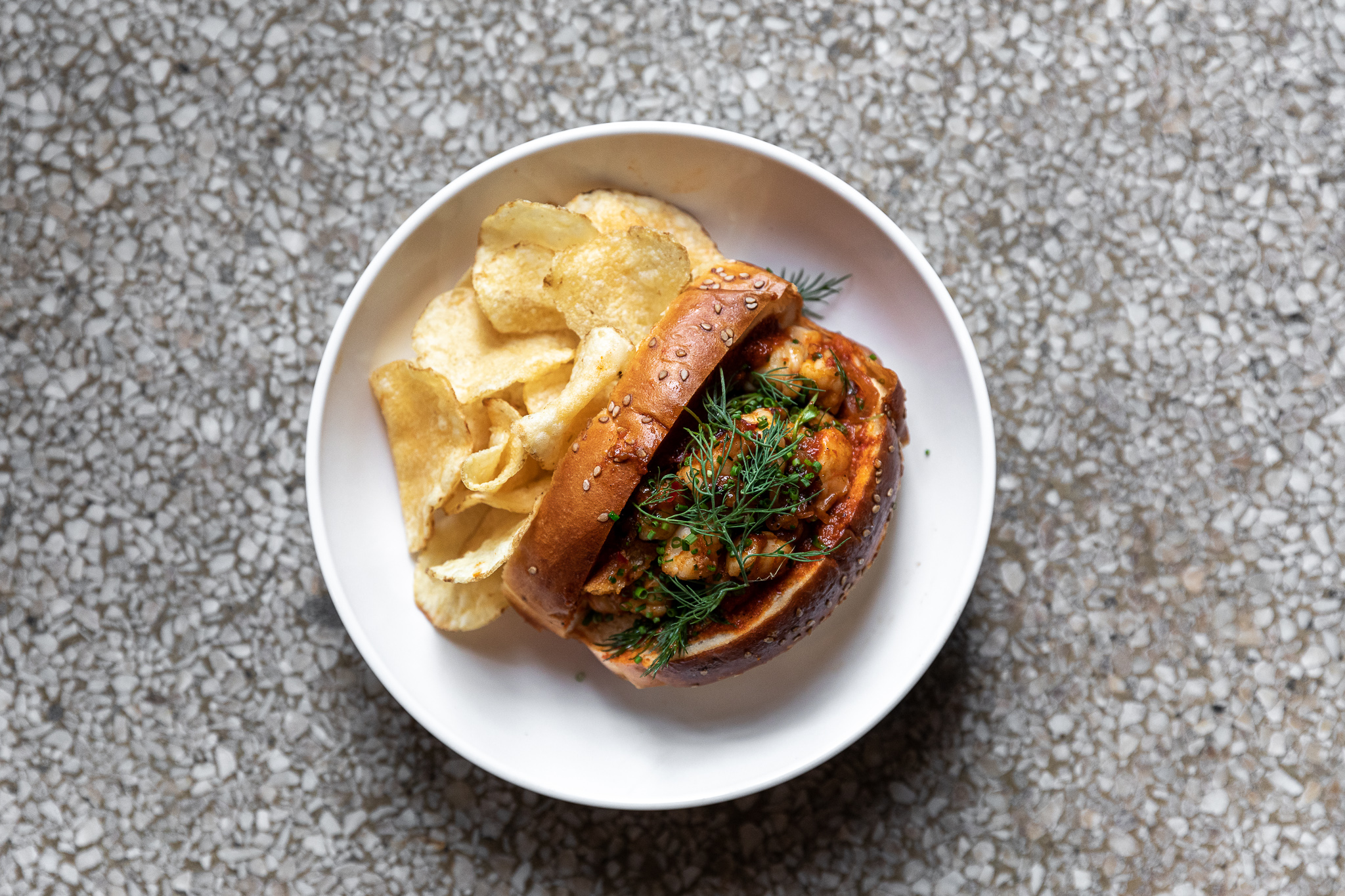 A shrimp roll in a squishy, golden brown bun with sesame seeds, a red shrimp filling and green herbs. It's sitting on a white plate next to a pile of potato chips.