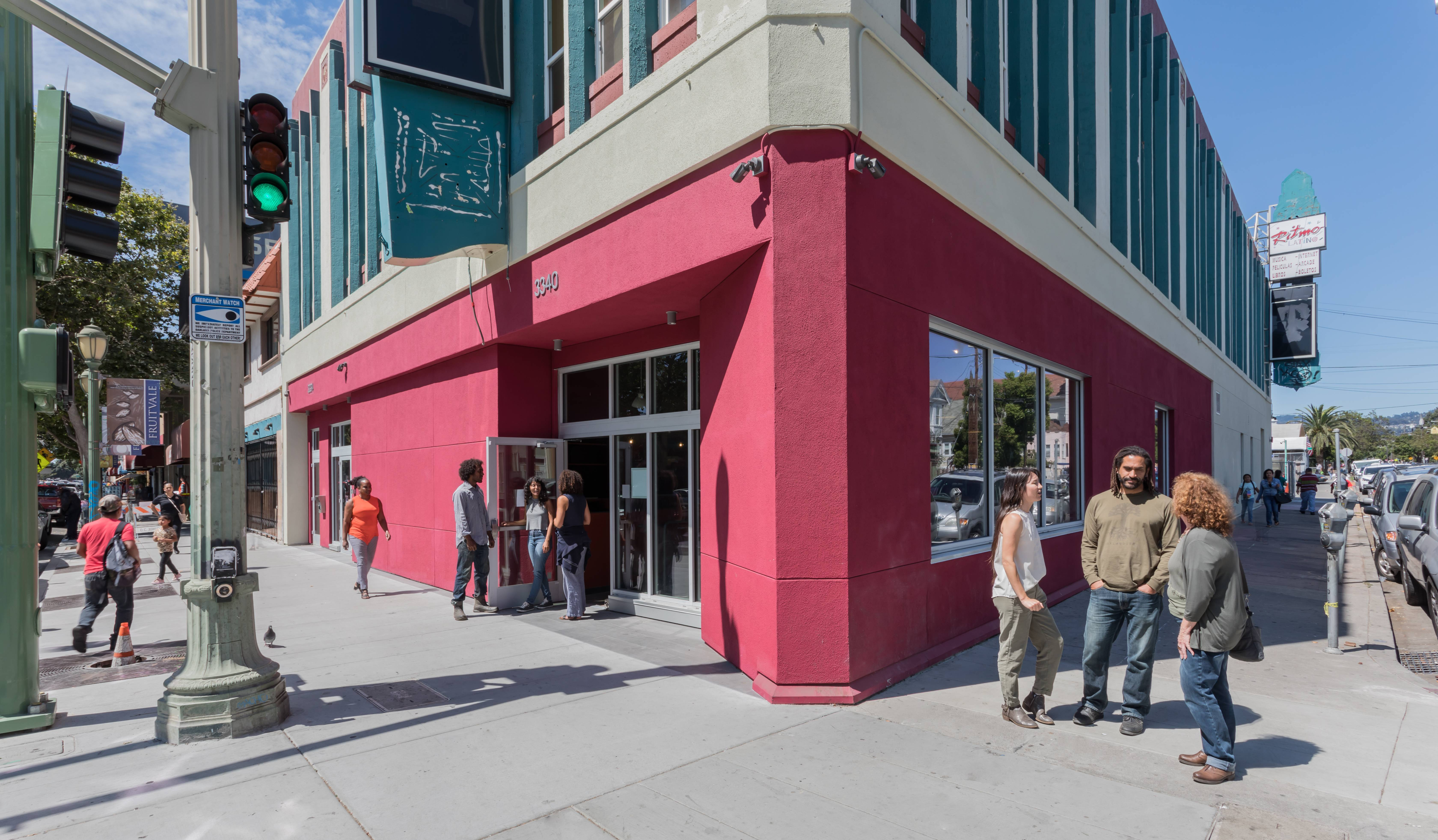 A building painted magenta and teal located on a street corner with a group of men and women standing in front of it, engaged in conversation.