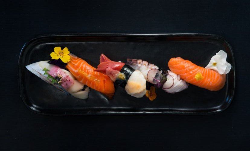 Top-down view of five pieces of nigiri on a black plate, garnished with flowers and ginger.