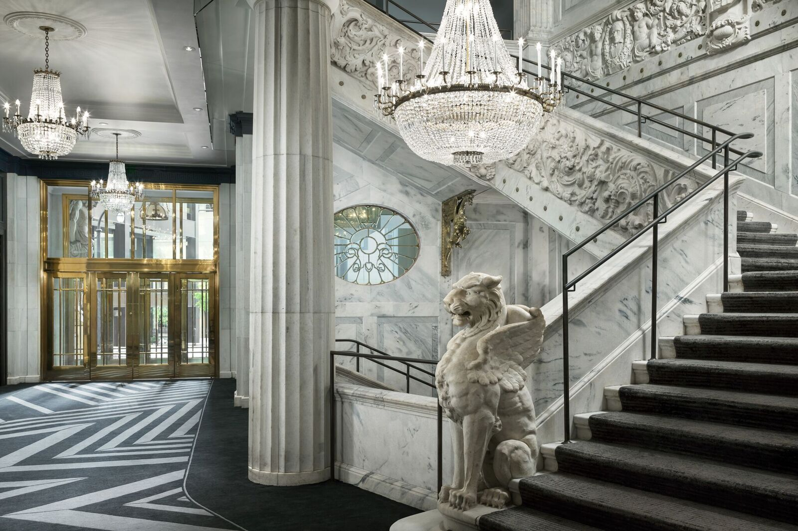 An opulent hotel lobby of marble and crystal.
