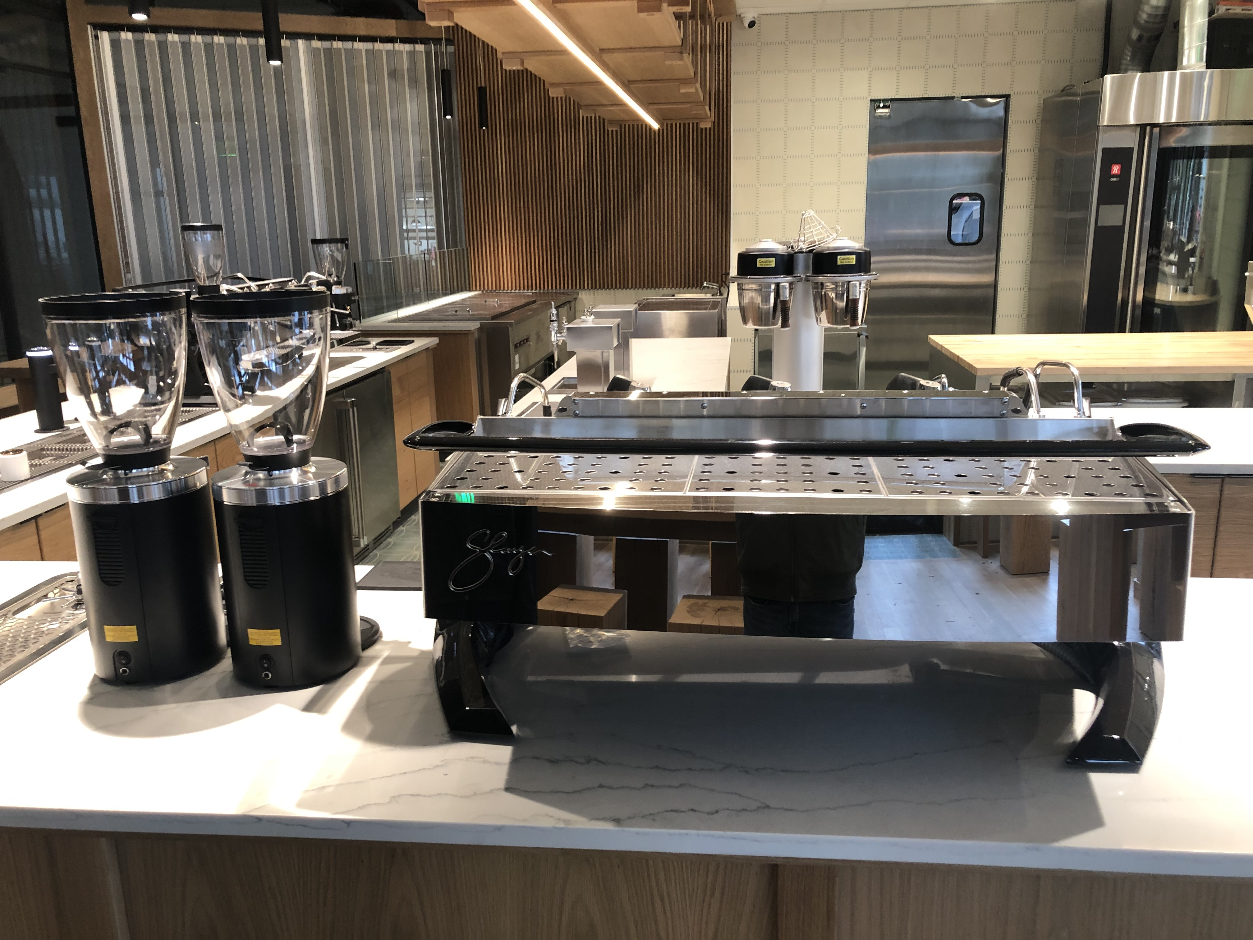 A photo of espresso-making equipment, including a large espresso machine, on the counter at Kaffe Landskap