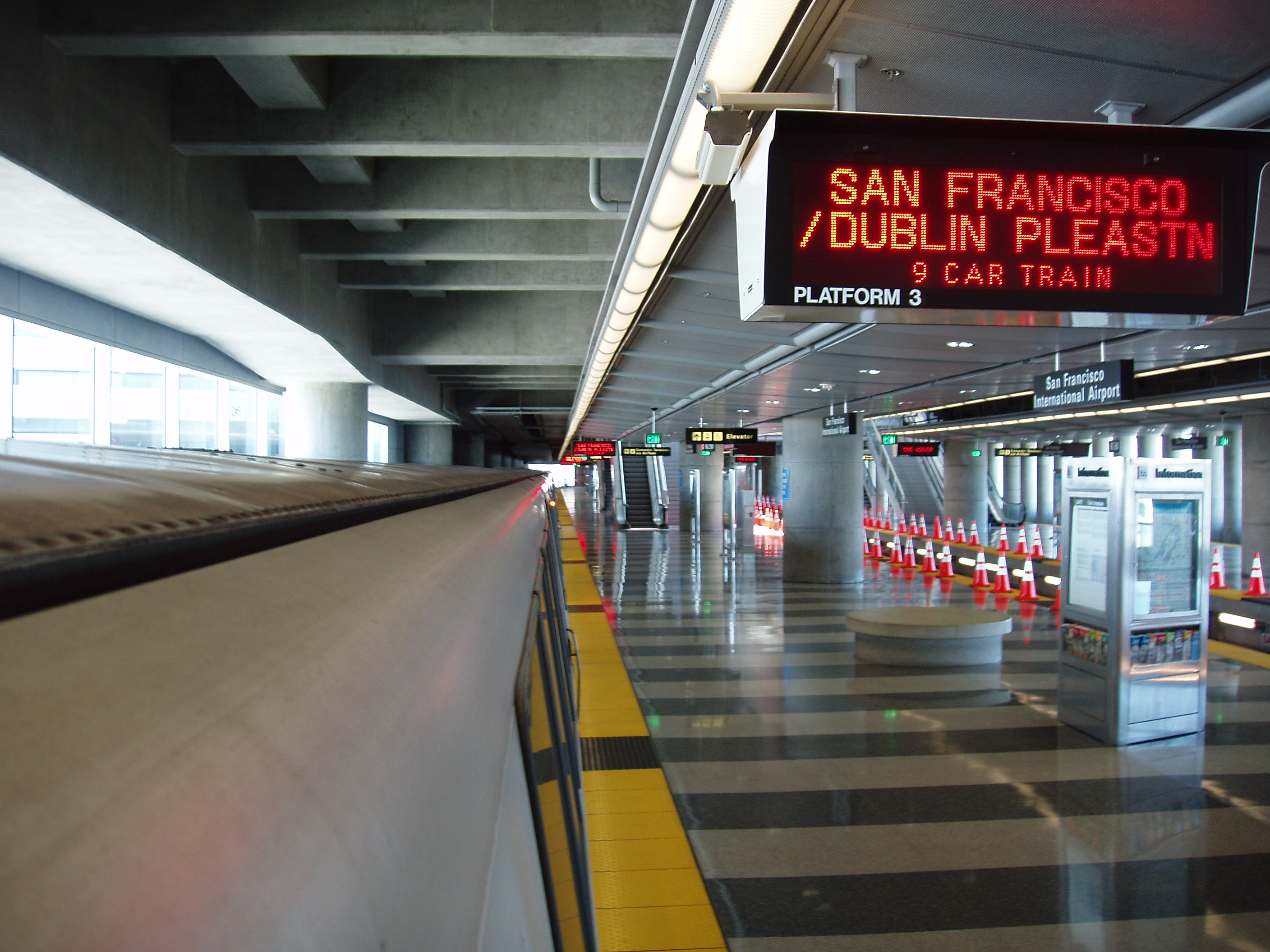 An empty train platform, with a red digital sign advertising trips to San Francisco and Dublin.