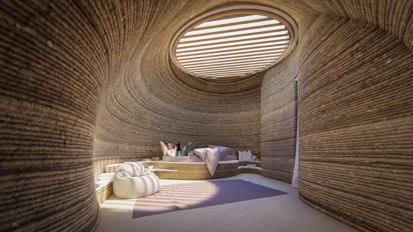 Rendering of person laying on bed in 3d-printed home with curvy brown walls and a round skylight up top.