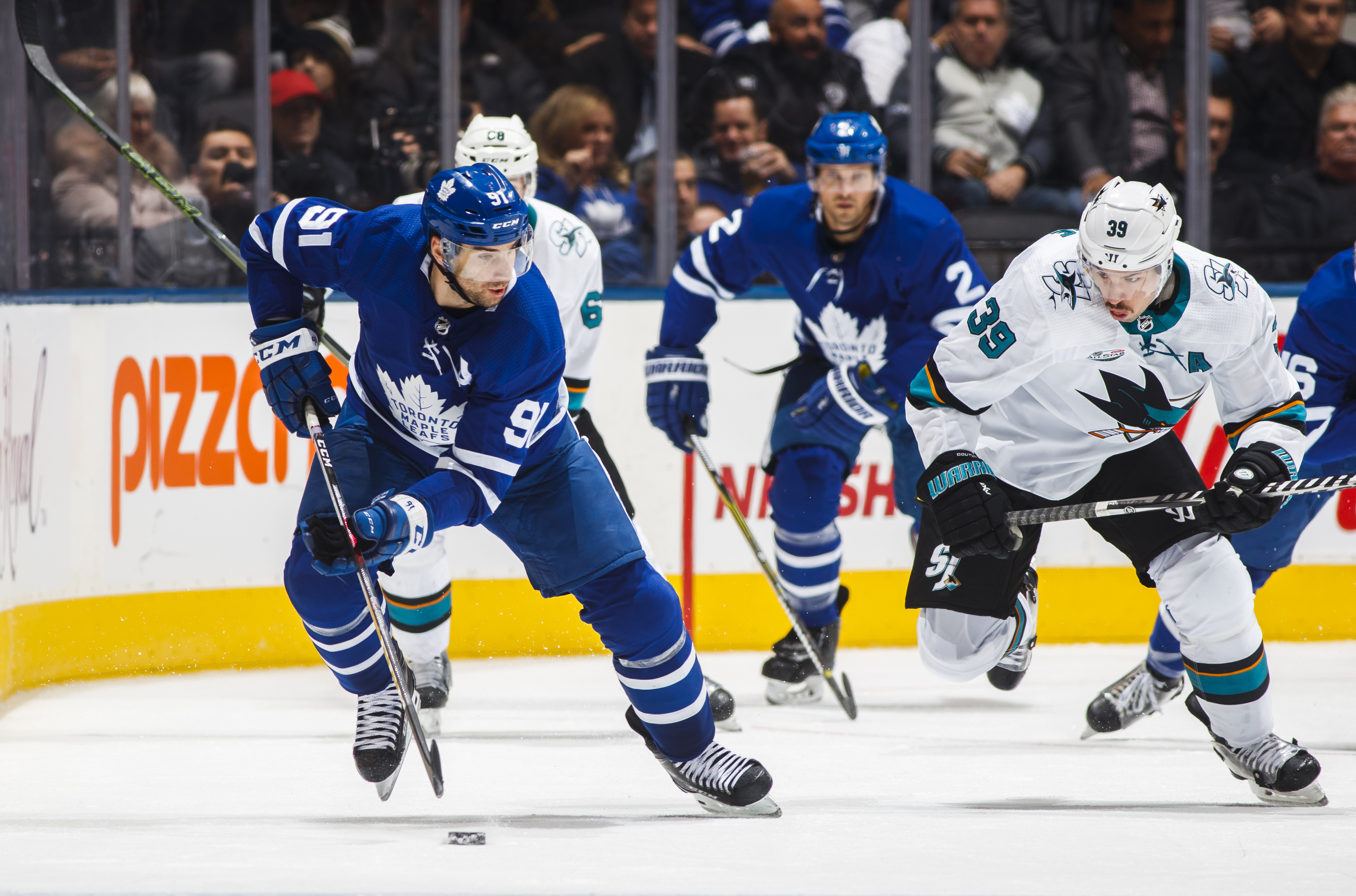 John Tavares #91 of the Toronto Maple Leafs skates against Logan Couture #39 of the San Jose Sharks during the third period at the Scotiabank Arena on November 28, 2018 in Toronto, Ontario, Canada.
