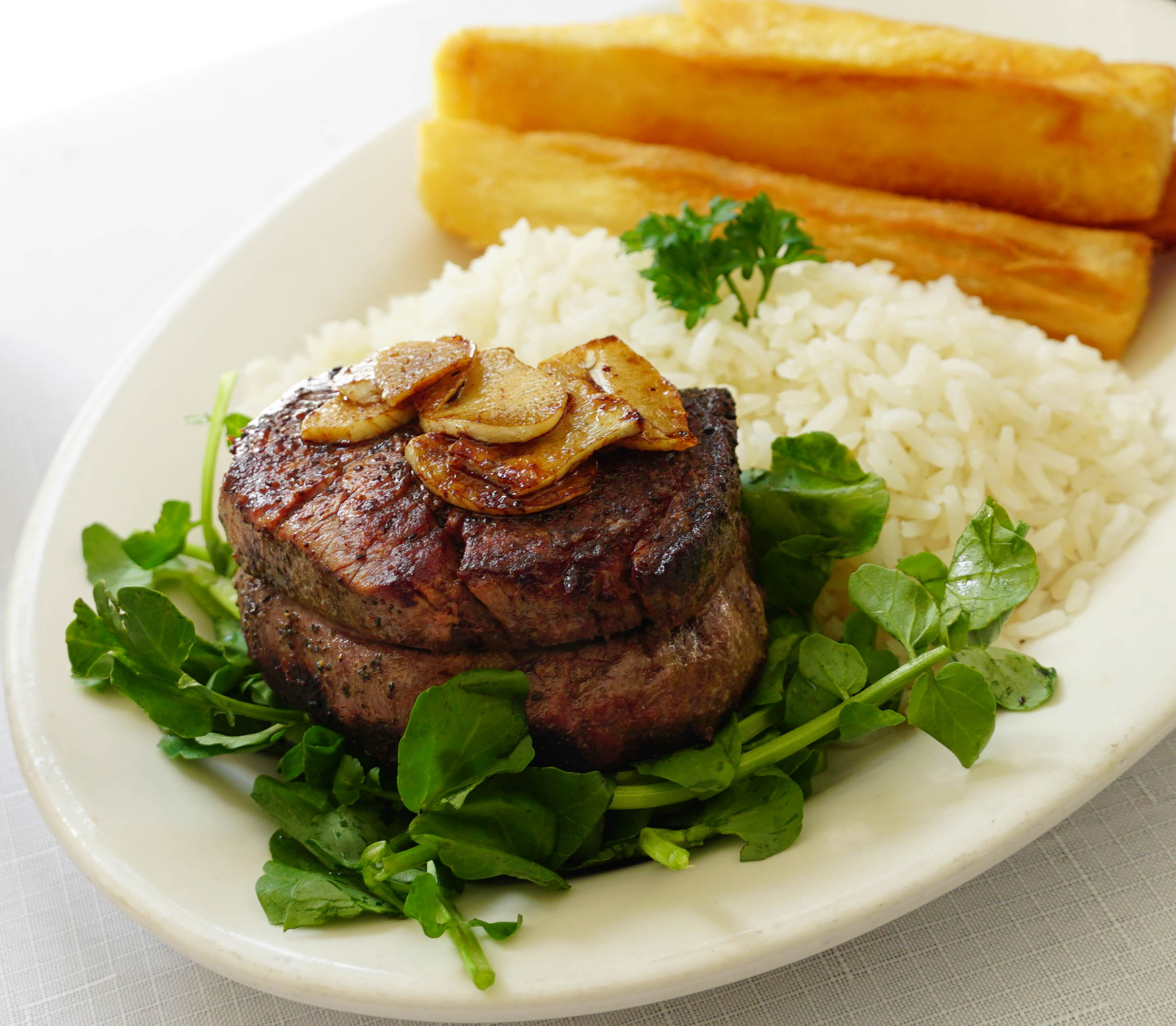 Steak, rice, and yuca fries plated on a white dish