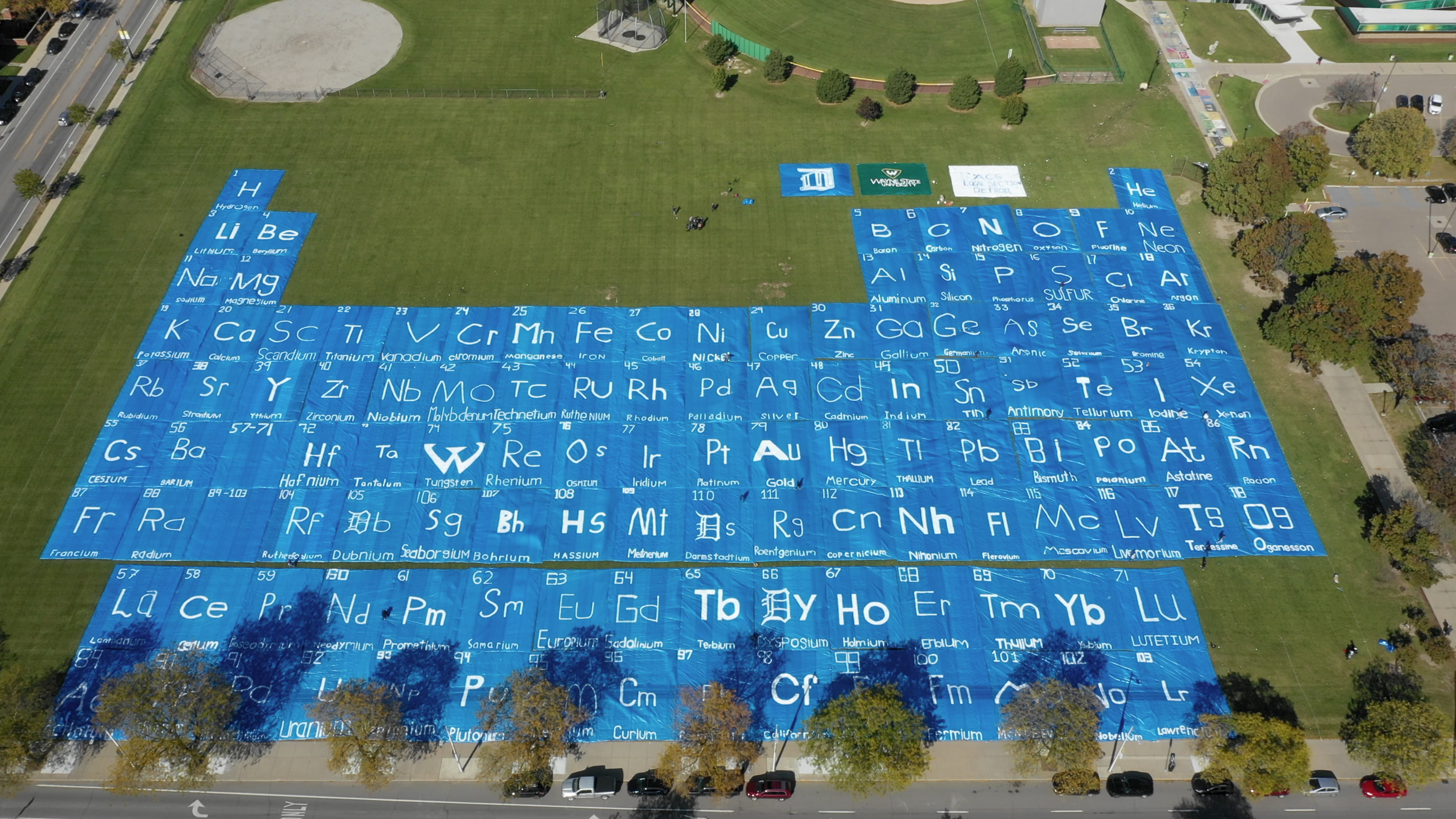 From high above, blue tarps with the chemical elements painted in each square.