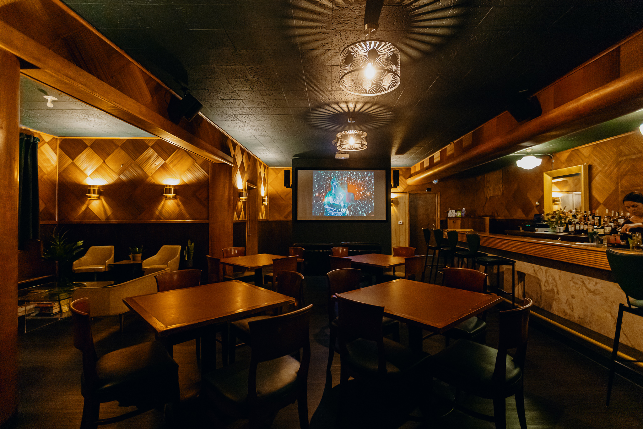 A dimly lit room with four-top tables, a bar, and floor-to-ceiling wood paneled walls.