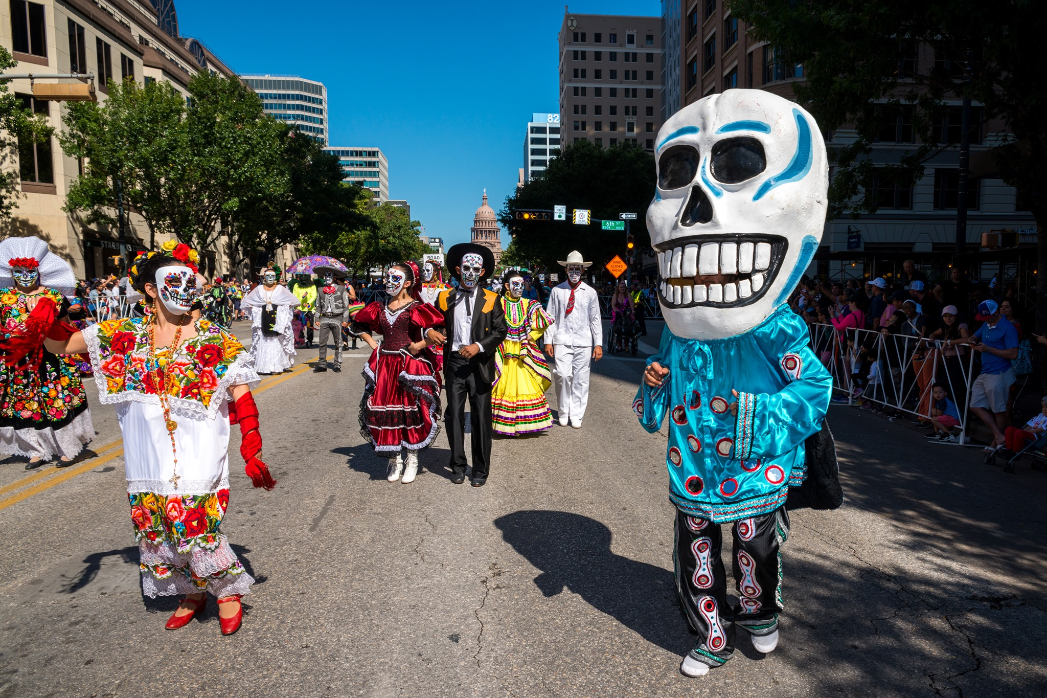 A city street with people dressed in traditional clothing for Dias de los Muertos, including people with their faces painted as skeletons and wearing wedding dresses and suits. One person has on an oversized skeleton puppet head.